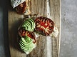 Croissant with tomatoes and avocado on a chopping board