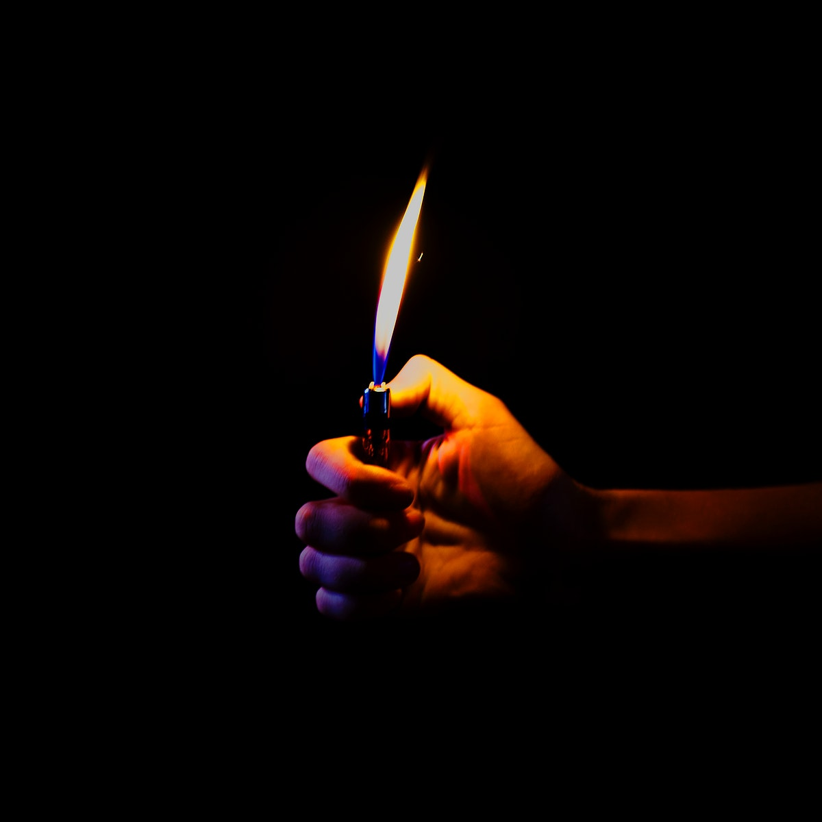 Hand holding a lit lighter in the dark