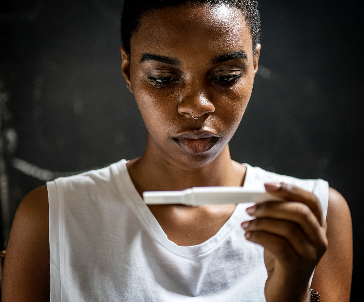 Closeup of black woman with pregnancy test in a hand