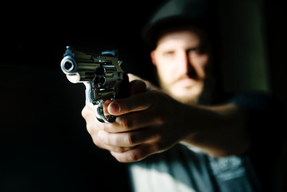 Man holding a gun with black background