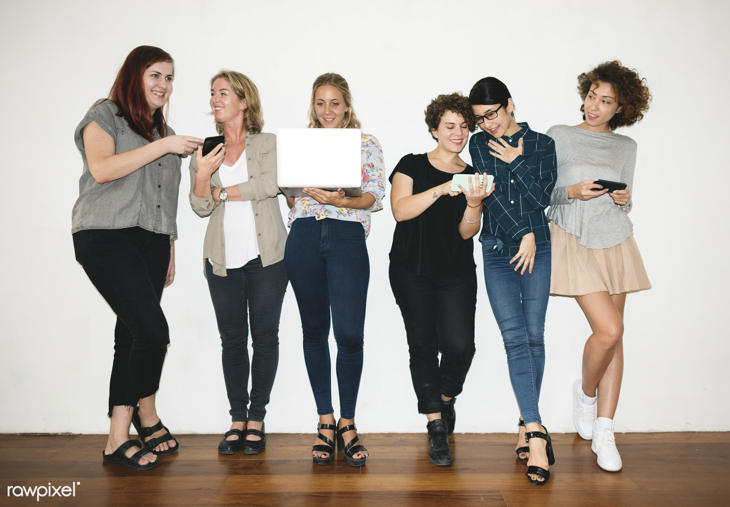 A cheerful fashion designers team - adult, casual clothing, diverse, fashion, friends, laptop, man, mobile, posing for...