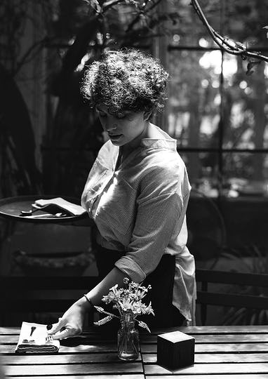 Black and white portrait of a woman working in a cafe