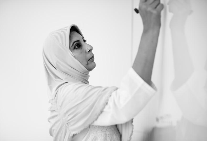 A Muslim teacher is writing a white board