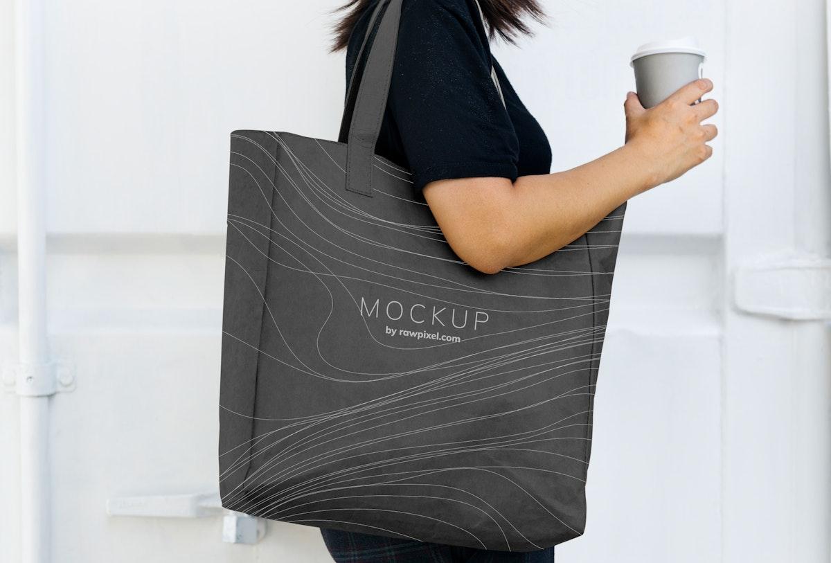 Woman carrying a black shopping bag mockup