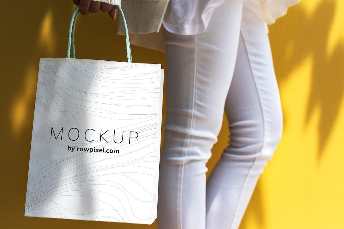 Woman holding a shopping bag mockup