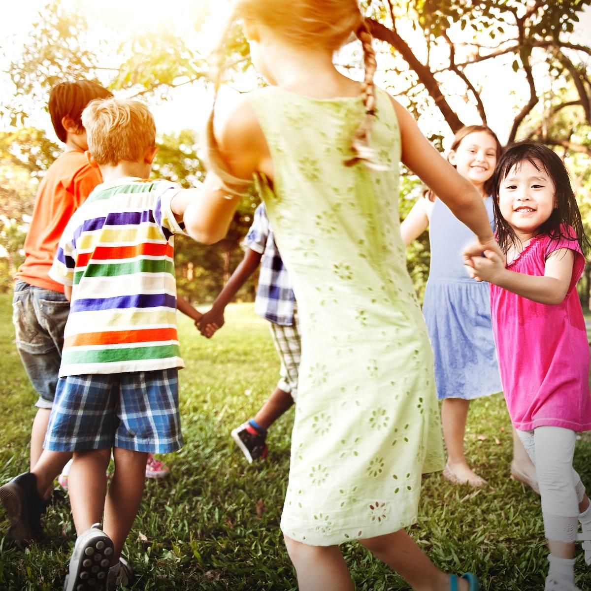 Cute diverse kids dancing in the park