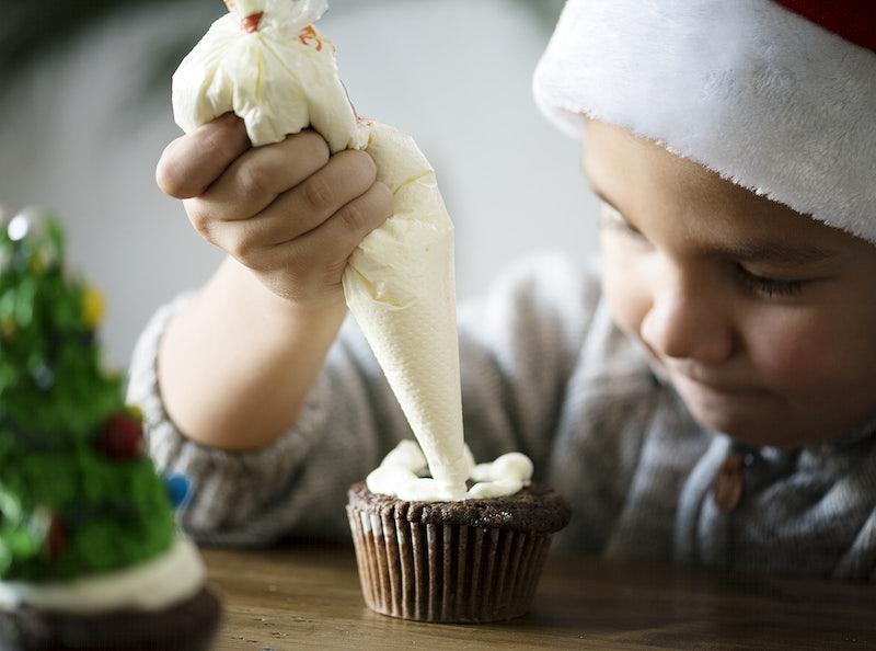 Little boy adding icing on a cupcake