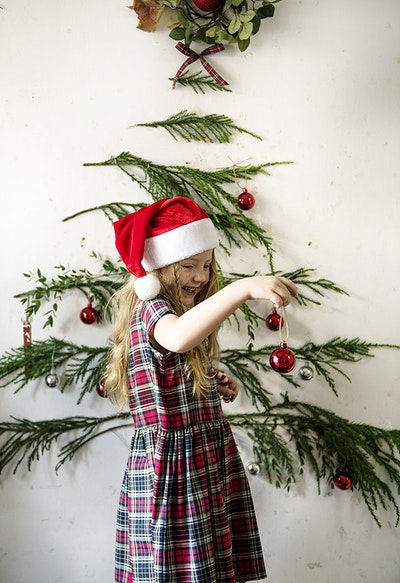 a1c0ae897e32c Girl wearing a santa hat hanging up Christmas ornaments