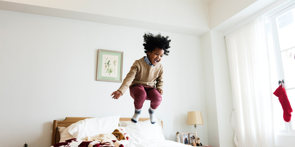Young happy kid having fun jumping up and down on a bed social banner