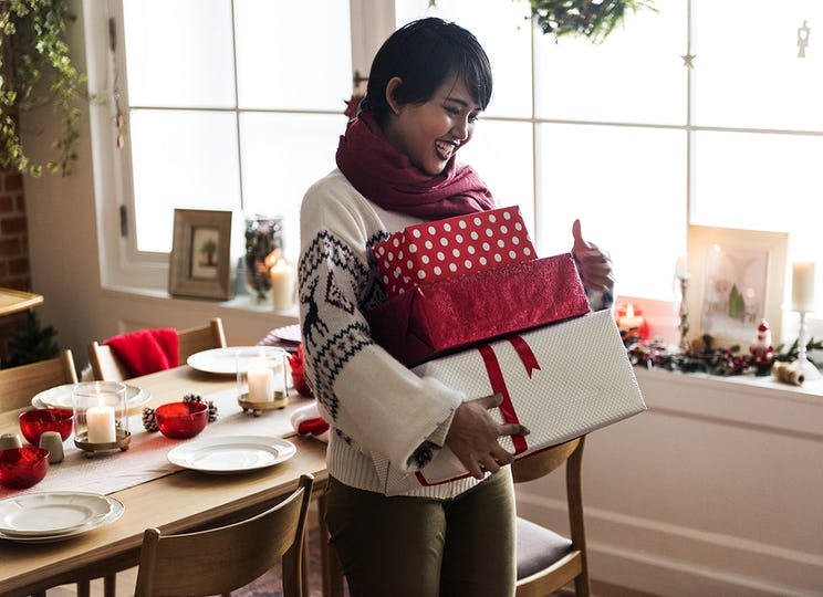 An Asian woman carrying Christmas gift boxes