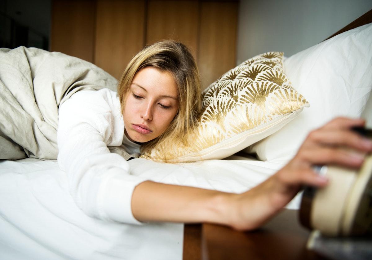 A sleepy Caucasian woman turning an alarm off