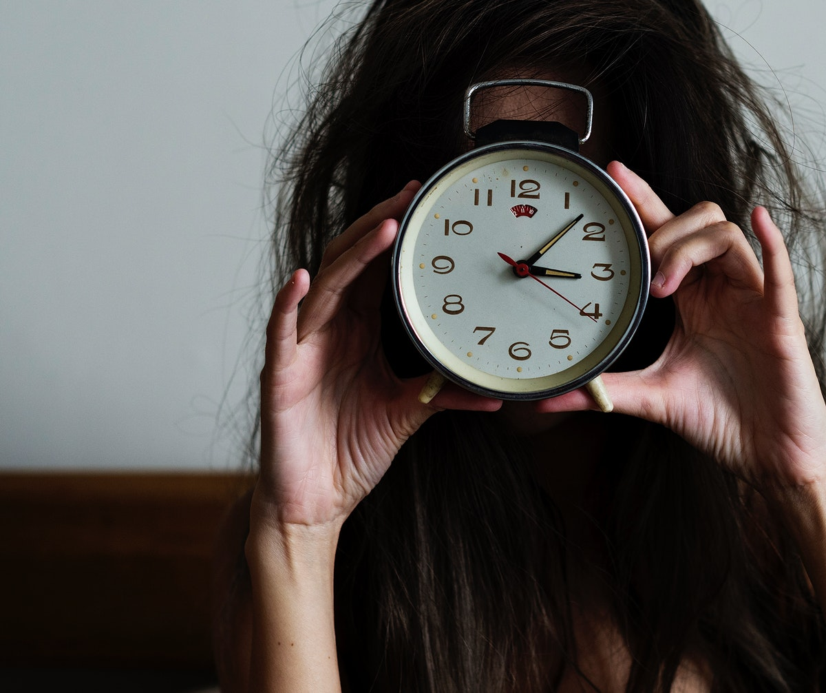 Messy hair girl wakes up with a clock
