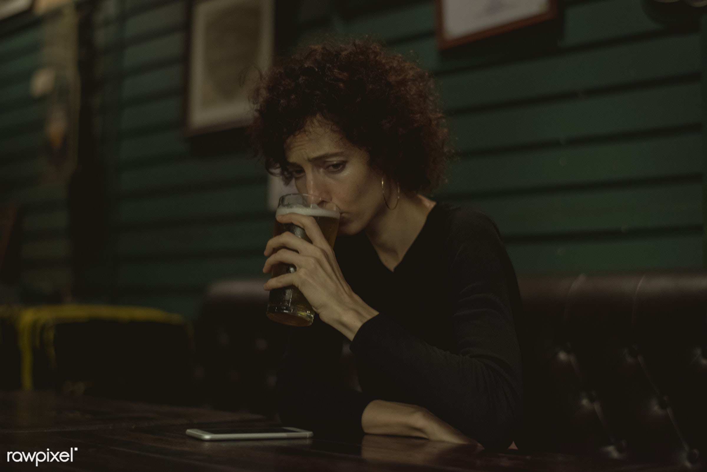 Woman having a beer at a bar - alcohol, alone, bar, beer, beverage, communication, connection, curly hair, dark, depressed,...