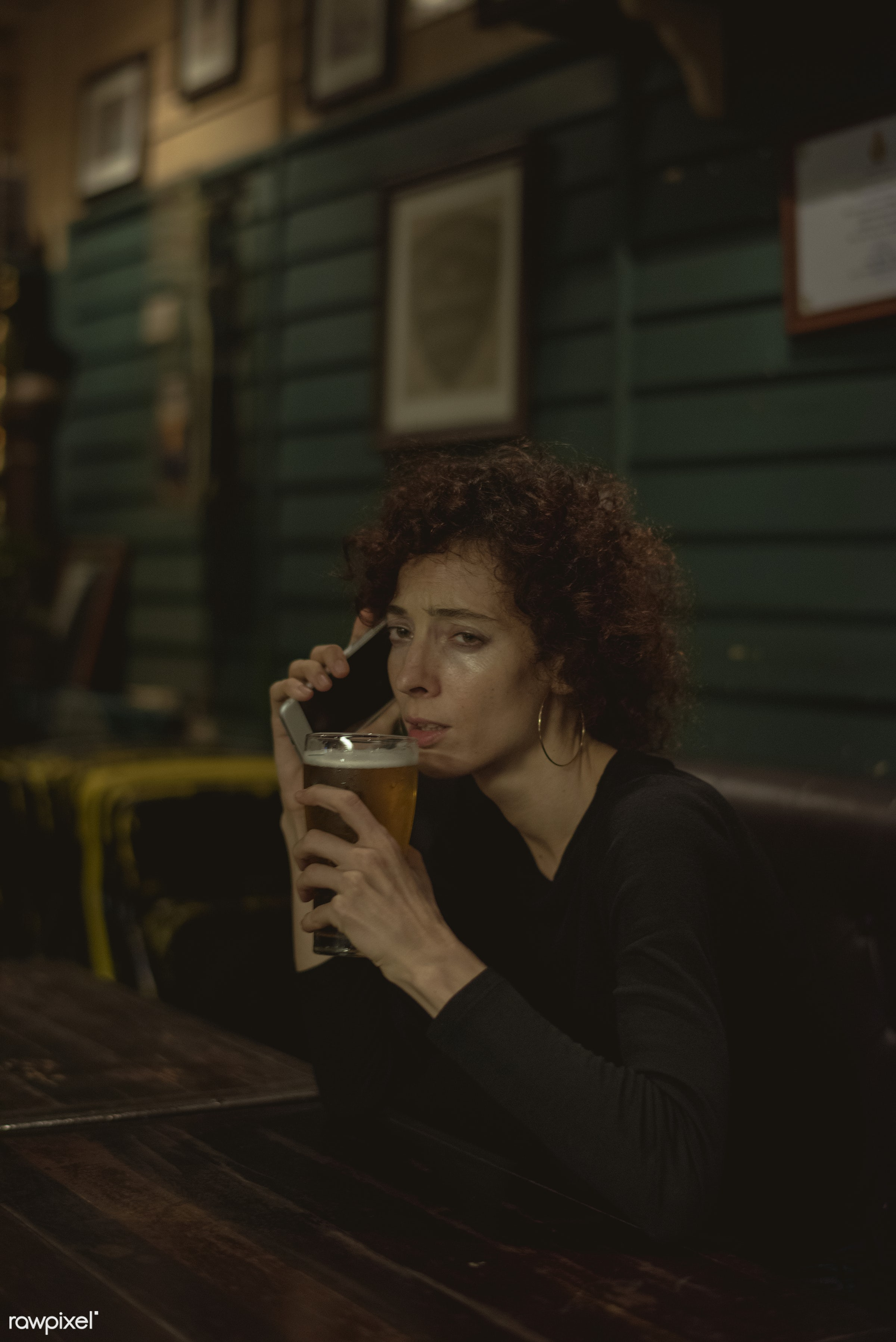 Woman having a beer at a bar - alcohol, alone, bar, beer, beverage, caucasian, communication, connection, curly hair, dark,...
