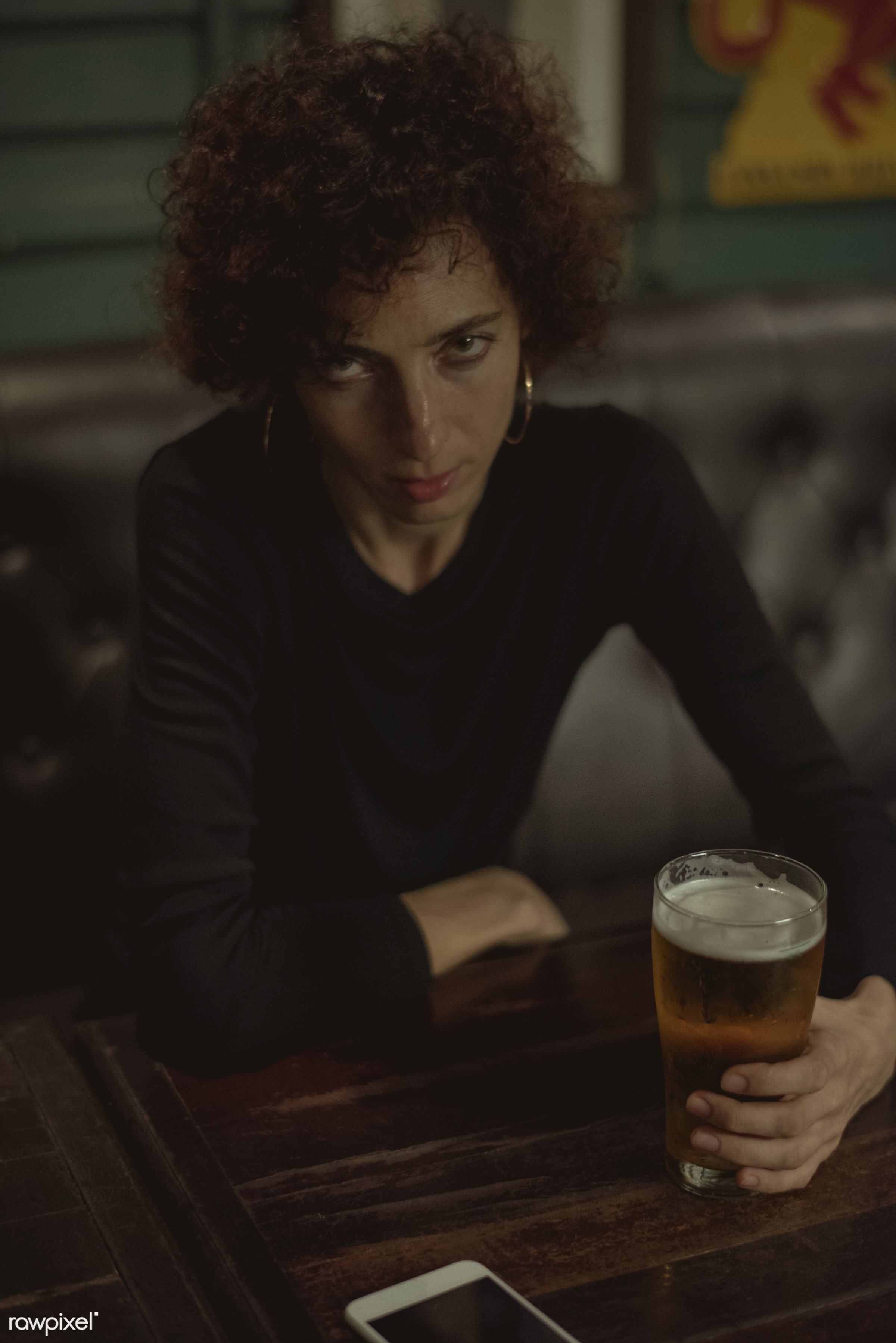 Woman having a beer at a bar - alcohol, alone, bar, beer, beverage, bored, communication, connection, curly hair, dark,...