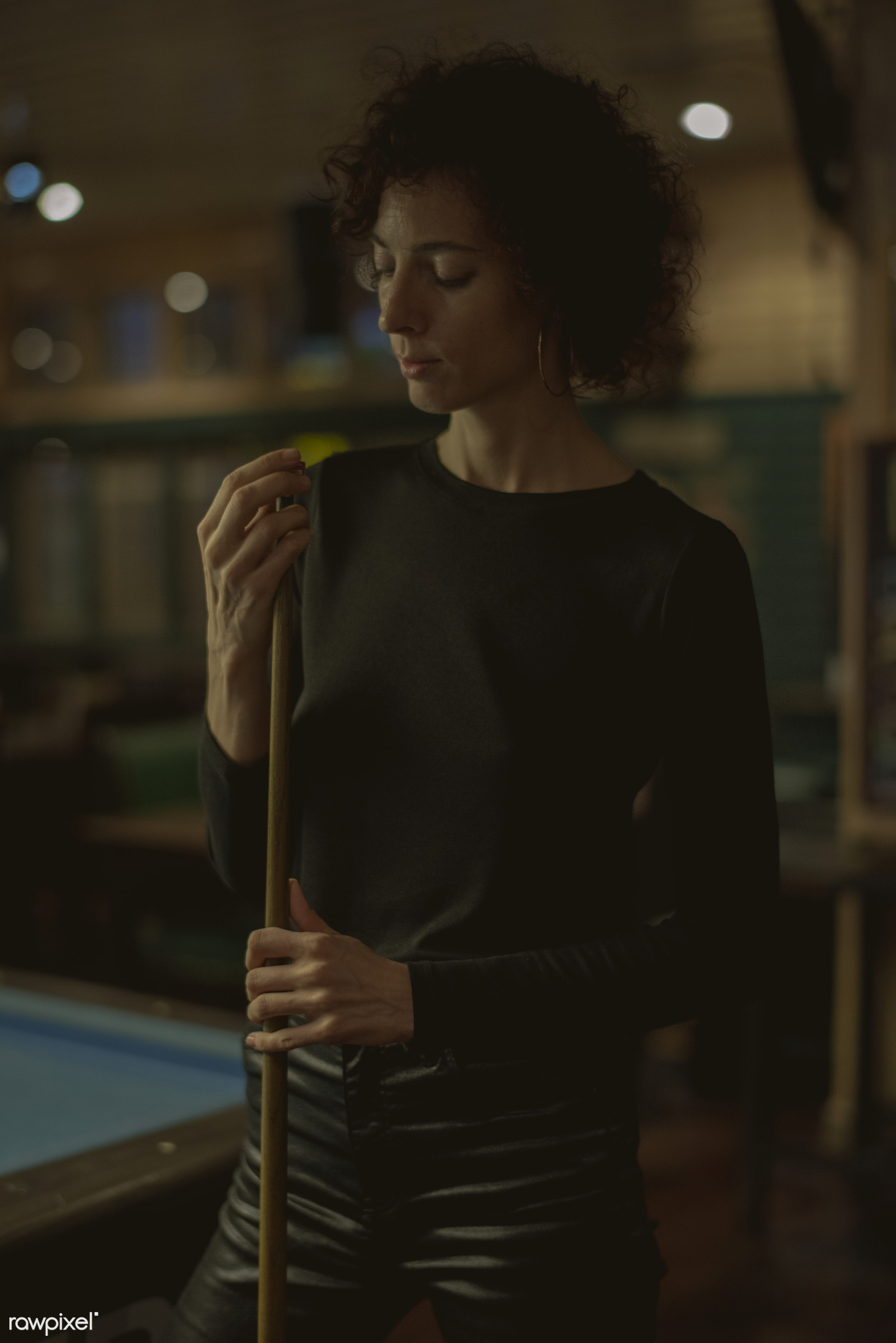 Woman playing pool at a bar - 8 ball, alone, bar, billiard, cue, curly hair, dark, entertain, game, lifestyle, night, night...