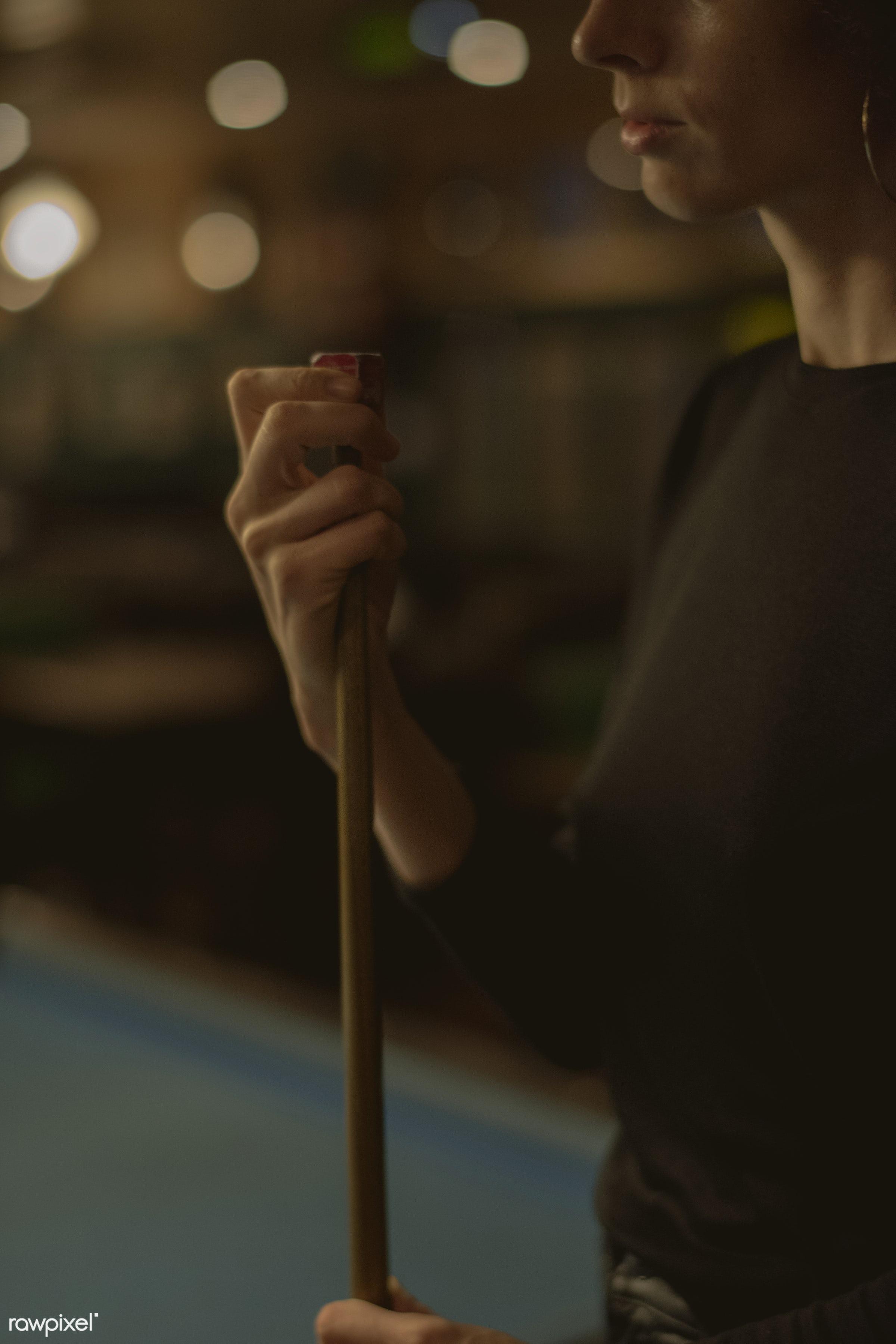 Woman playing pool at a bar - billiard, 8 ball, alone, bar, cue, curly hair, dark, entertain, game, lifestyle, night, night...