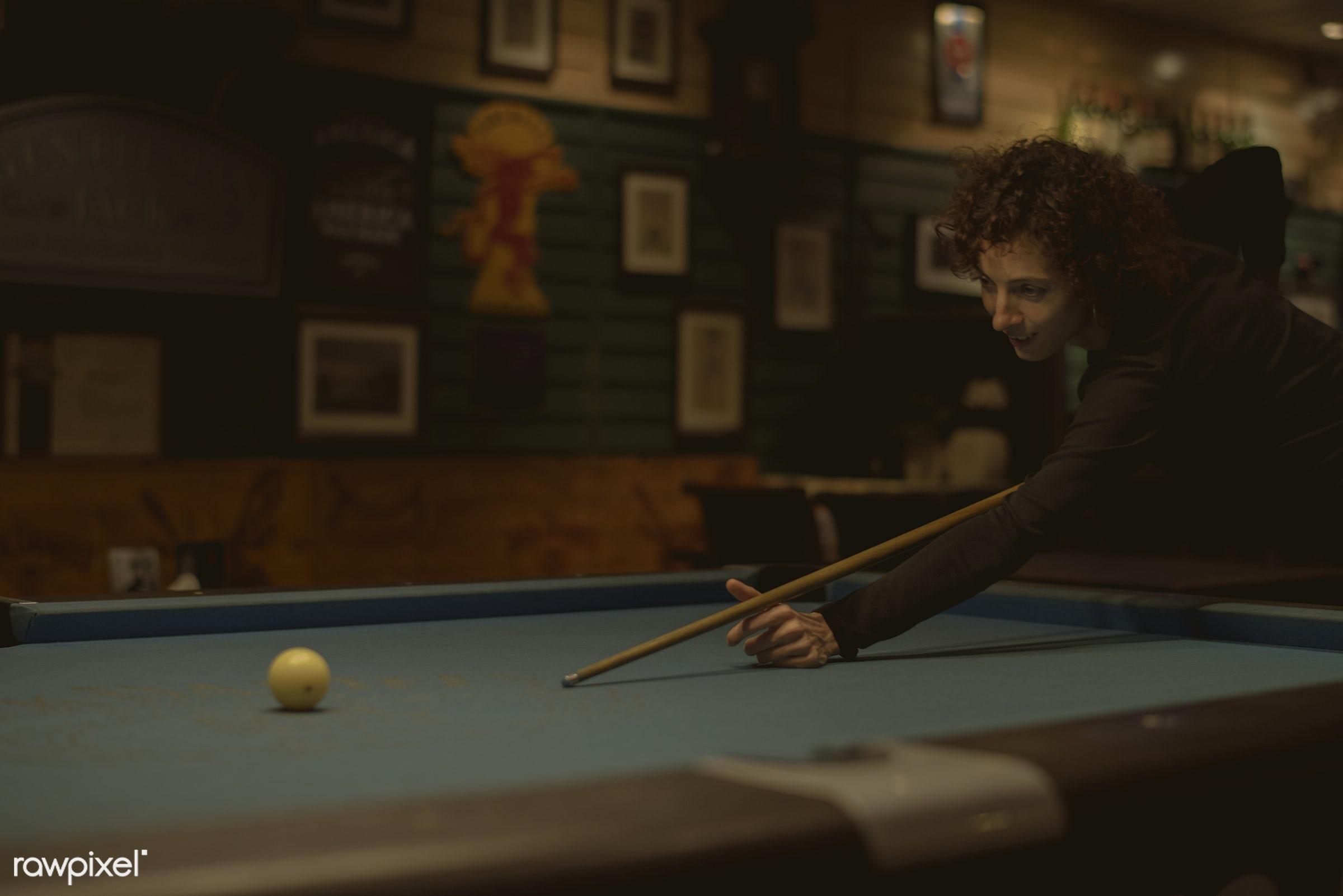 Woman playing pool at a bar - 8 ball, aiming, alone, balls, bar, billiard, caucasian, cue, curly hair, dark, enjoy,...