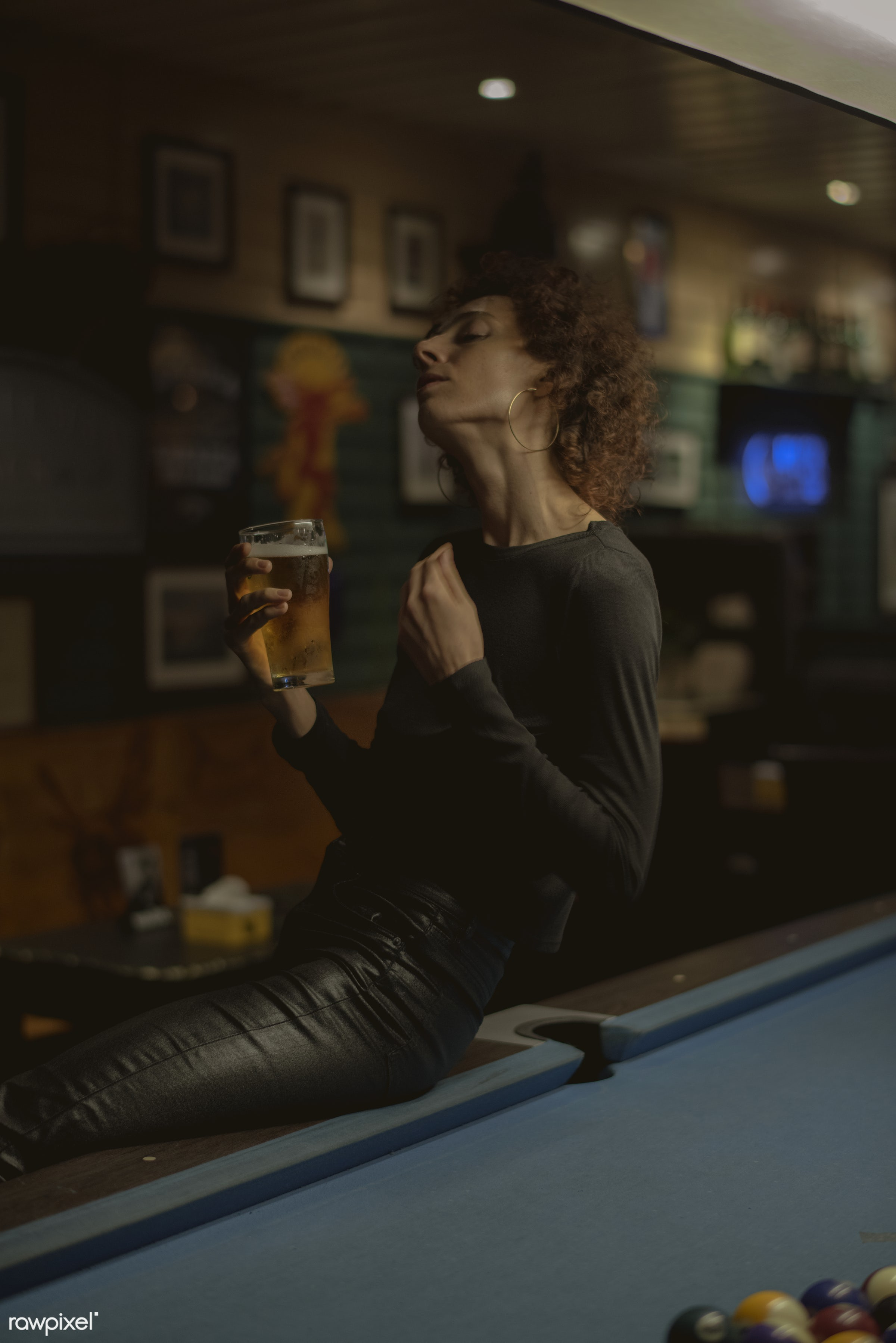 Woman having a beer at a bar - 8 ball, alcohol, alone, bar, beer, beverage, billiard, caucasian, cue, curly hair, dark,...