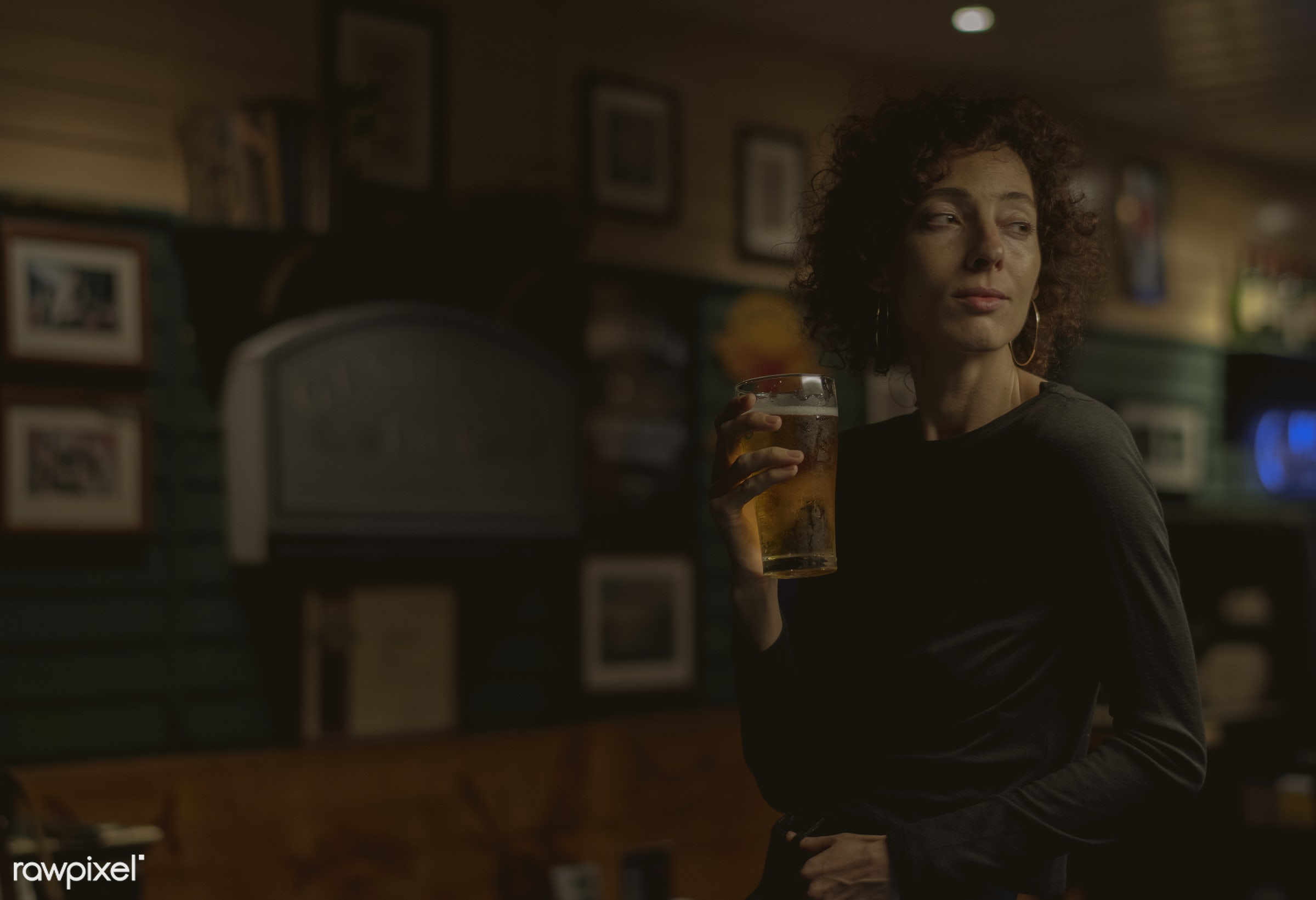 Woman having a beer at a bar - beer, lonely, alcohol, alone, bar, beverage, curly hair, dark, draft beer, drink, drinking,...