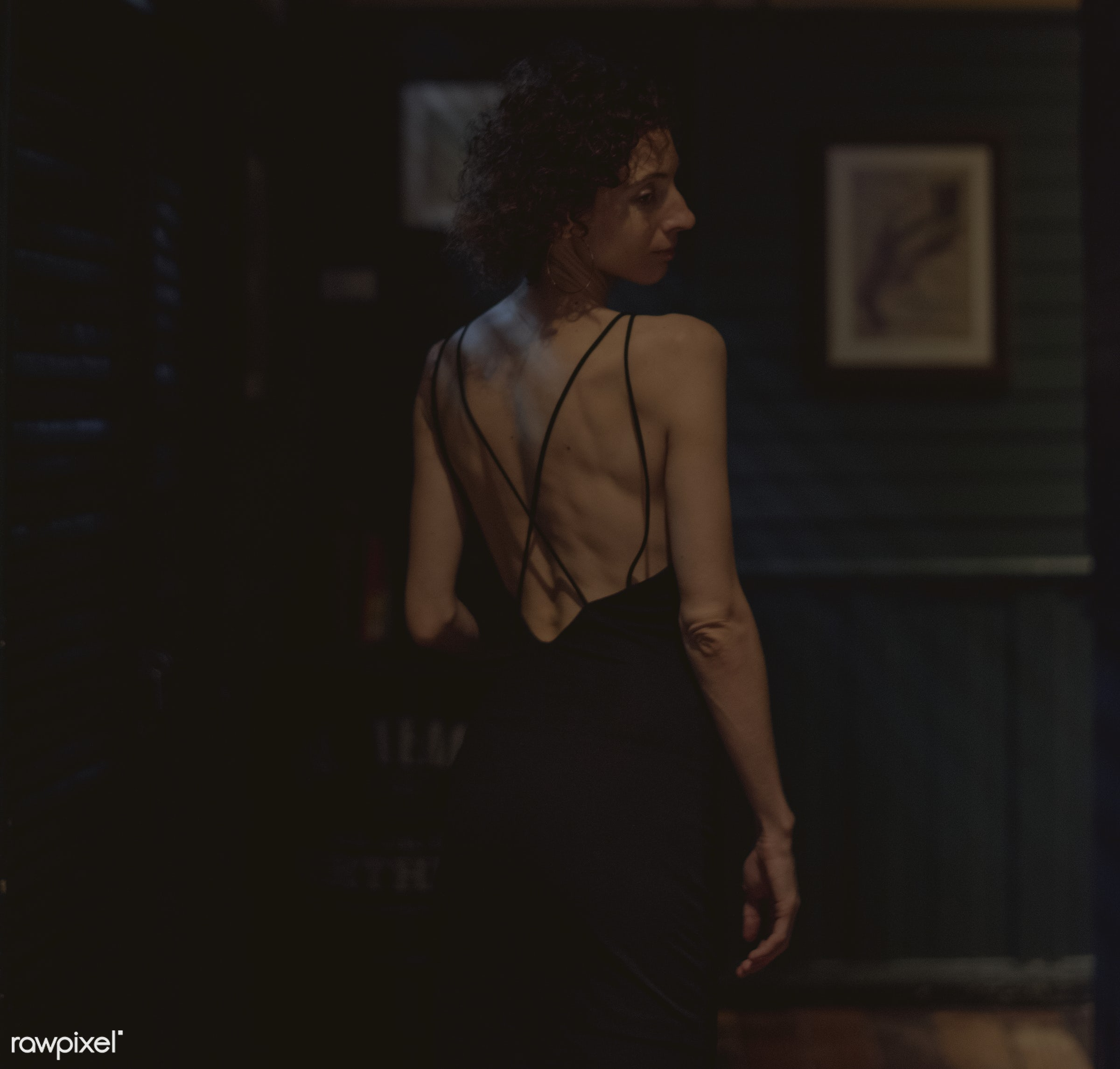 Portrait of a lone woman at a bar - alone, bar, curly hair, dark, lifestyle, night, night life, night out, one, people,...