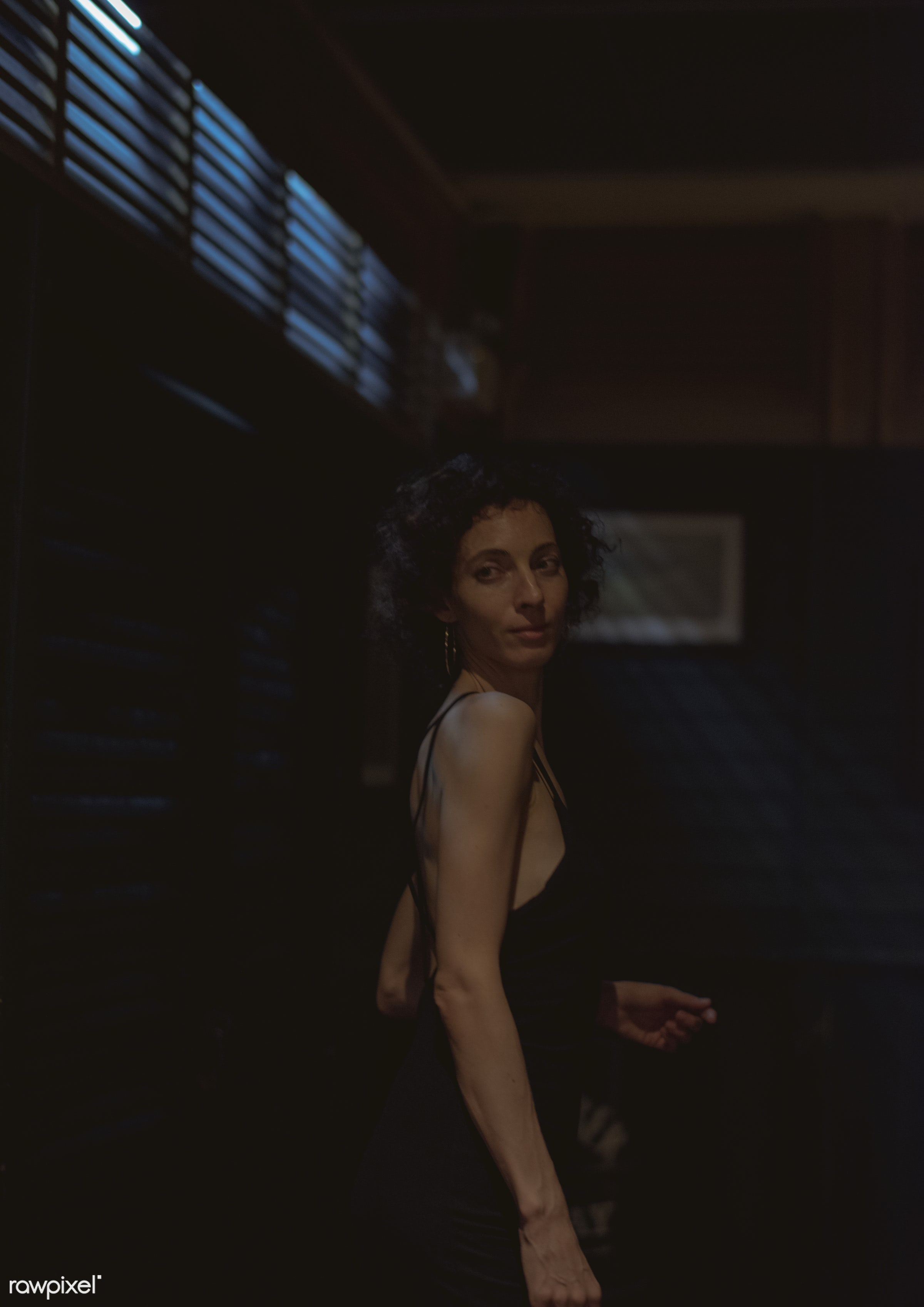 Portrait of solo woman at a bar - alone, bar, caucasian, curly hair, dark, lifestyle, night, night life, night out, one,...