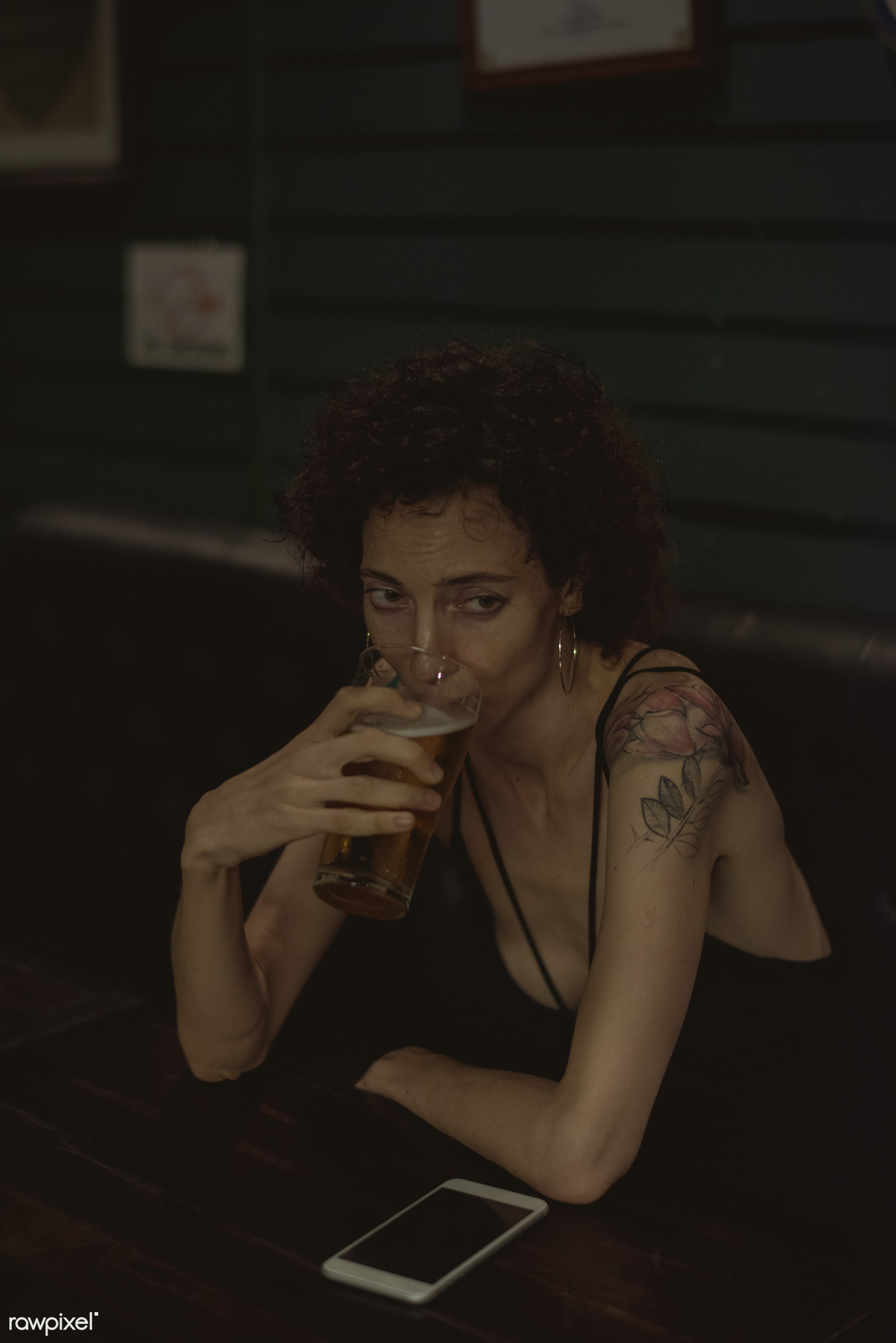 Lone woman having a beer at a bar - alcohol, alone, bar, beer, beverage, communication, connection, curly hair, dark, device...