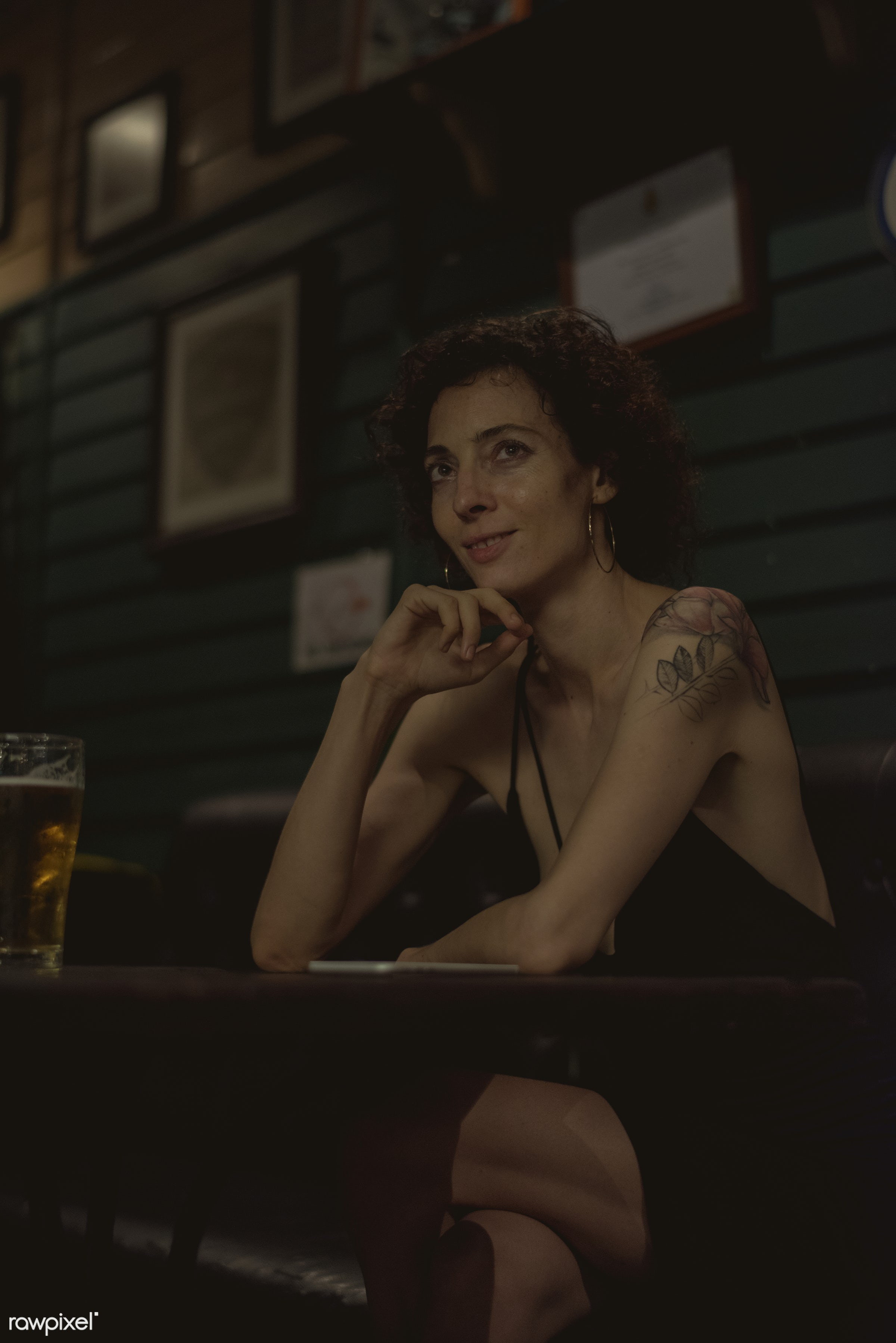 Portrait of a lone woman at a bar - alone, bar, cheerful, communication, connection, curly hair, dark, device, digital,...