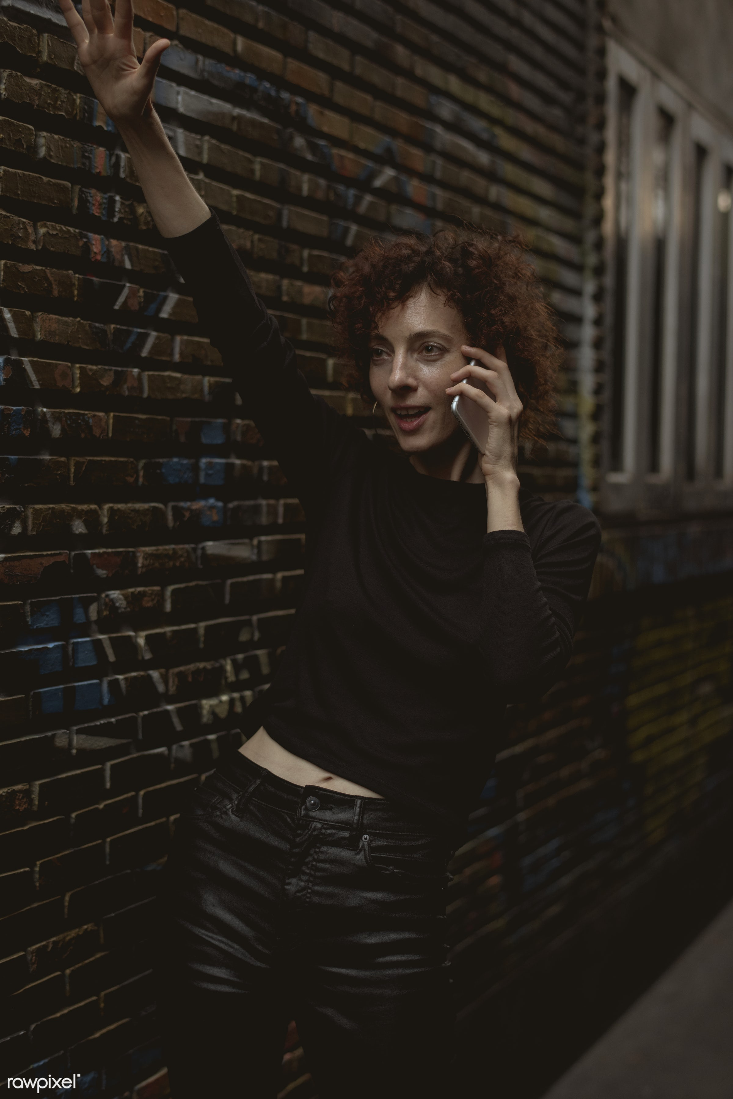 Woman talking on the phone - alley, alone, bar, calling, cheerful, communication, connection, curly hair, dark, device,...