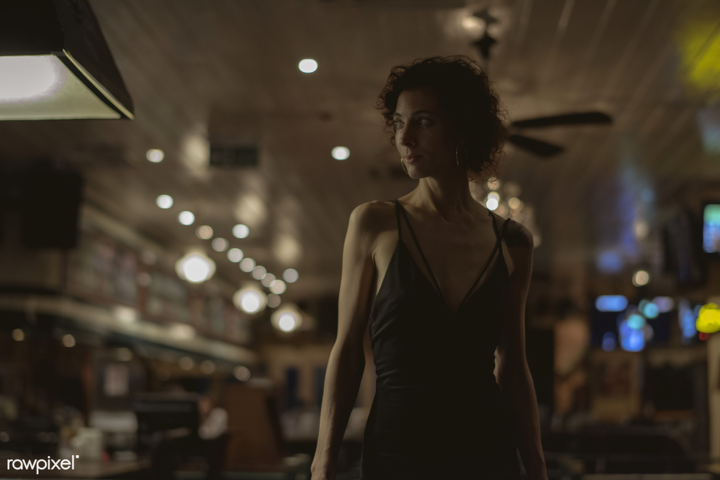 Portrait of solo woman at a bar - alone, bar, caucasian, curly hair, dark, emotion, expression, face, feeling, lifestyle,...