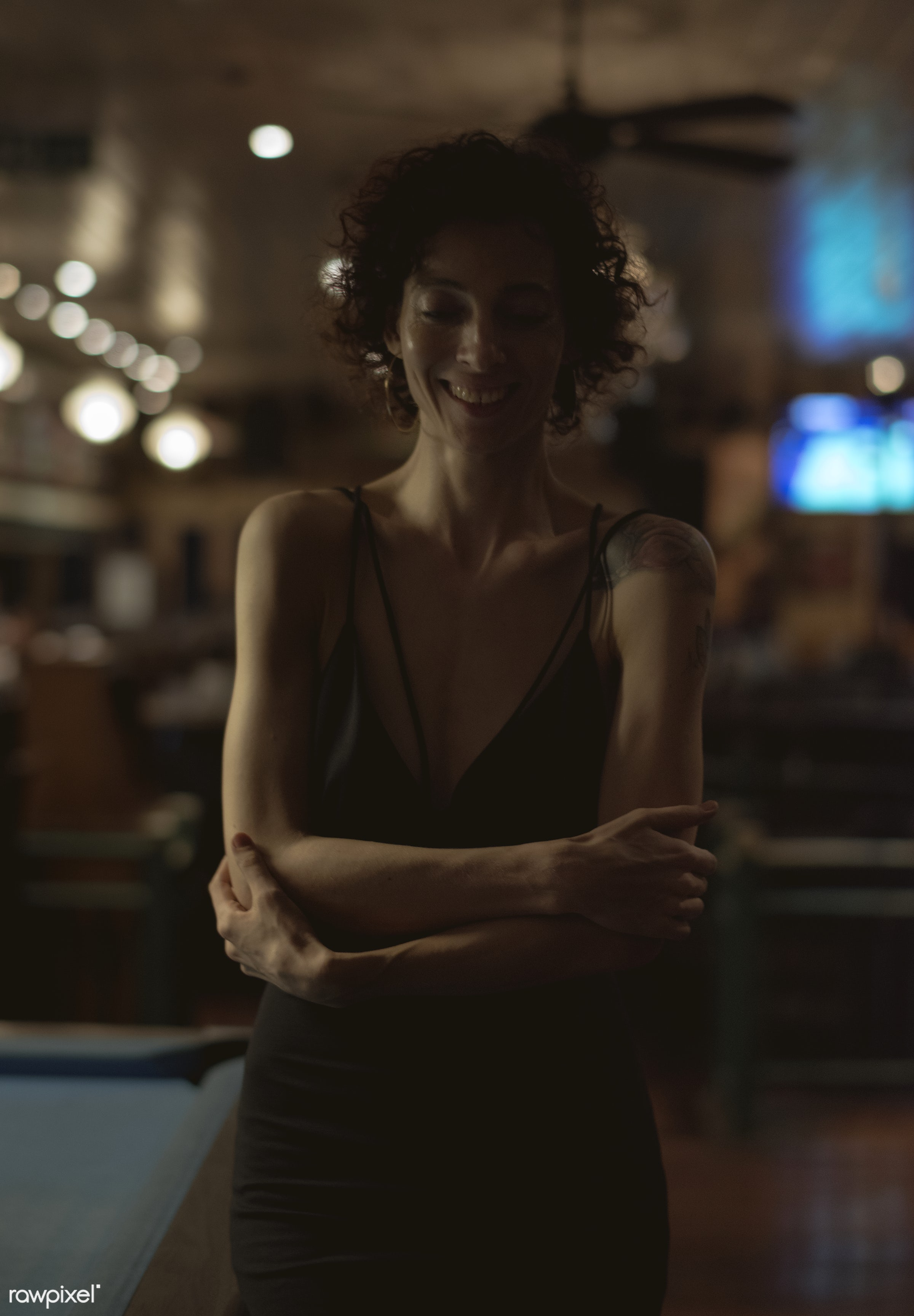 Portrait of a lone woman at a bar - 8 ball, alone, bar, caucasian, cheerful, curly hair, dark, happiness, happy, lifestyle,...