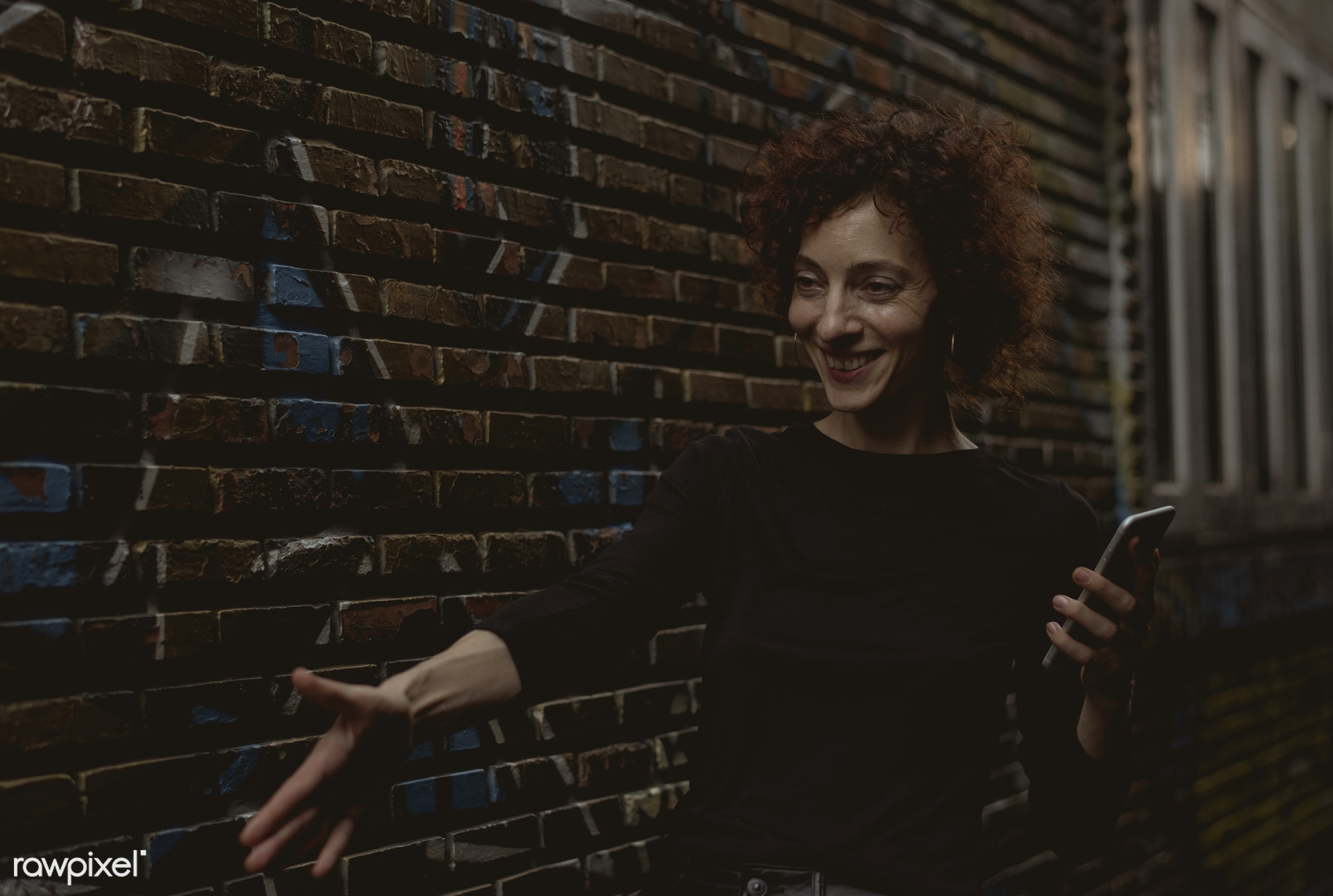 Woman reaching out her hand - alley, alone, bar, cheerful, communication, connection, curly hair, dark, device, digital,...