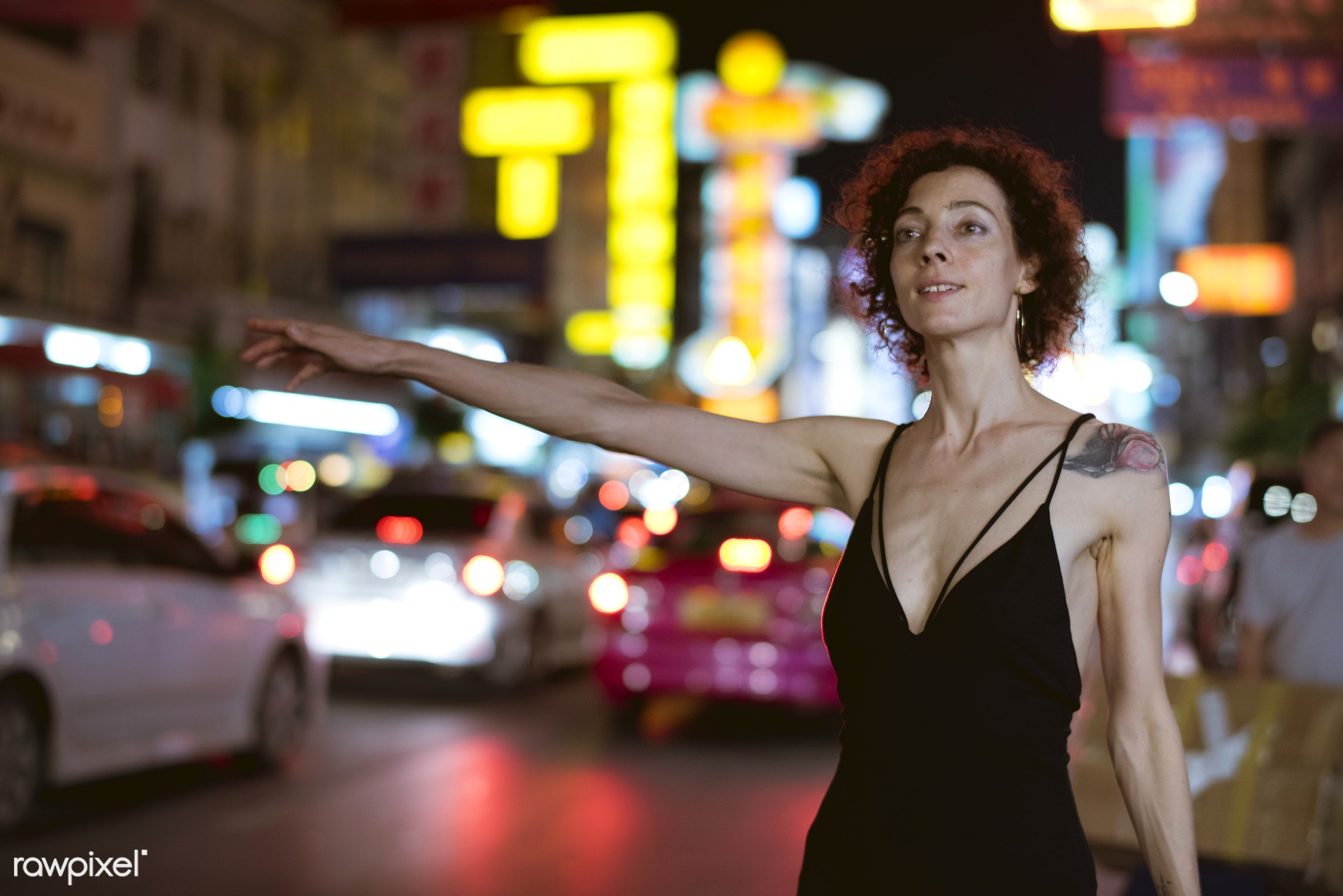 Woman hailing a cab - alone, busy, cab, calling, catching, caucasian, curly hair, dark, hailing, lifestyle, night, night...