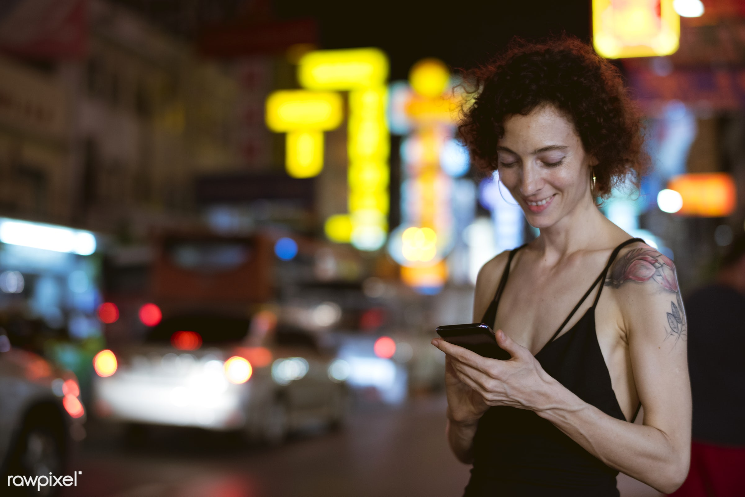 Woman standing by a busy street - cab, alone, calling, cheerful, communication, connection, curly hair, dark, device,...