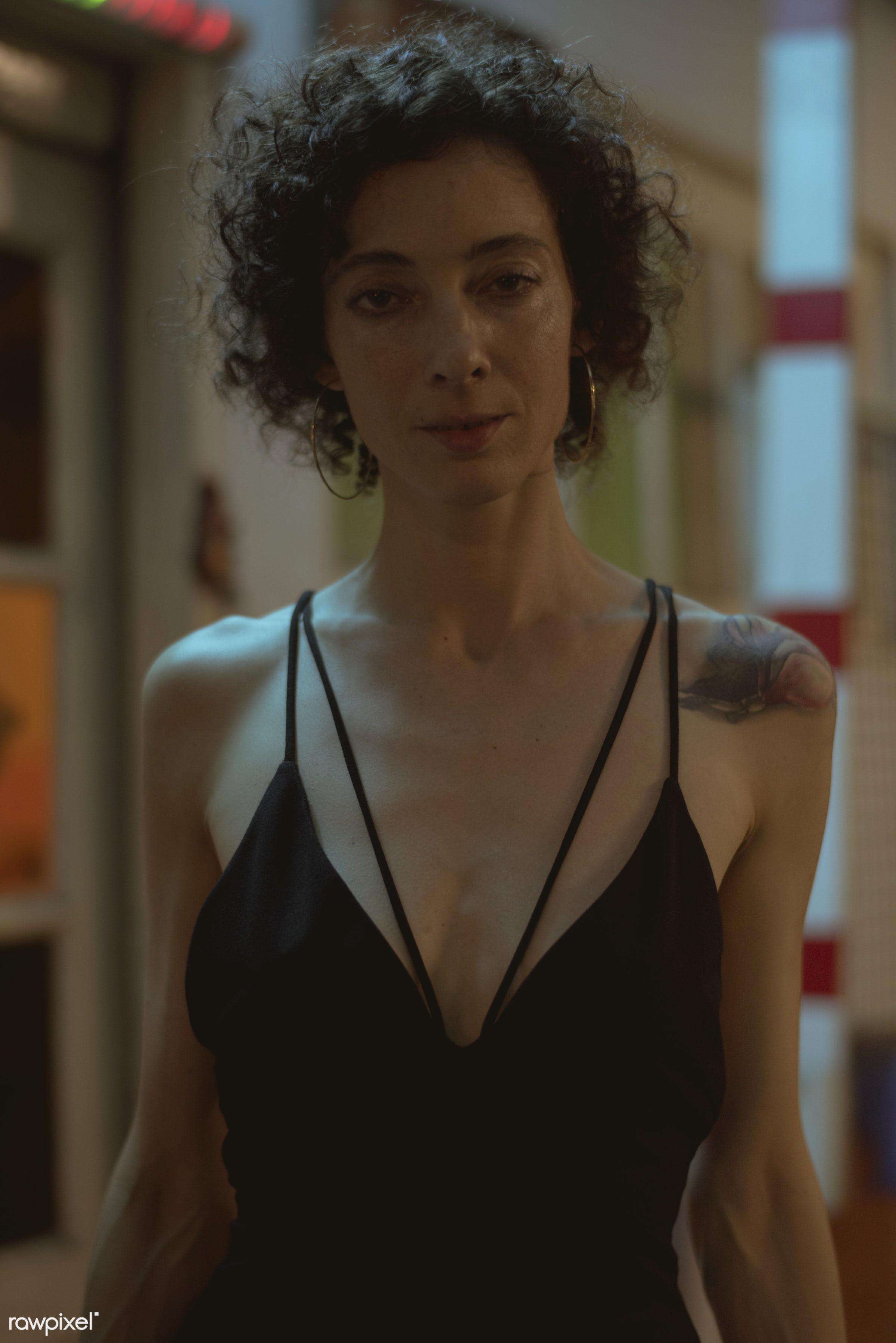 Portrait of a woman in a dark bar - alone, bar, club, clubbing, curly hair, dark, lifestyle, night, night life, night out,...