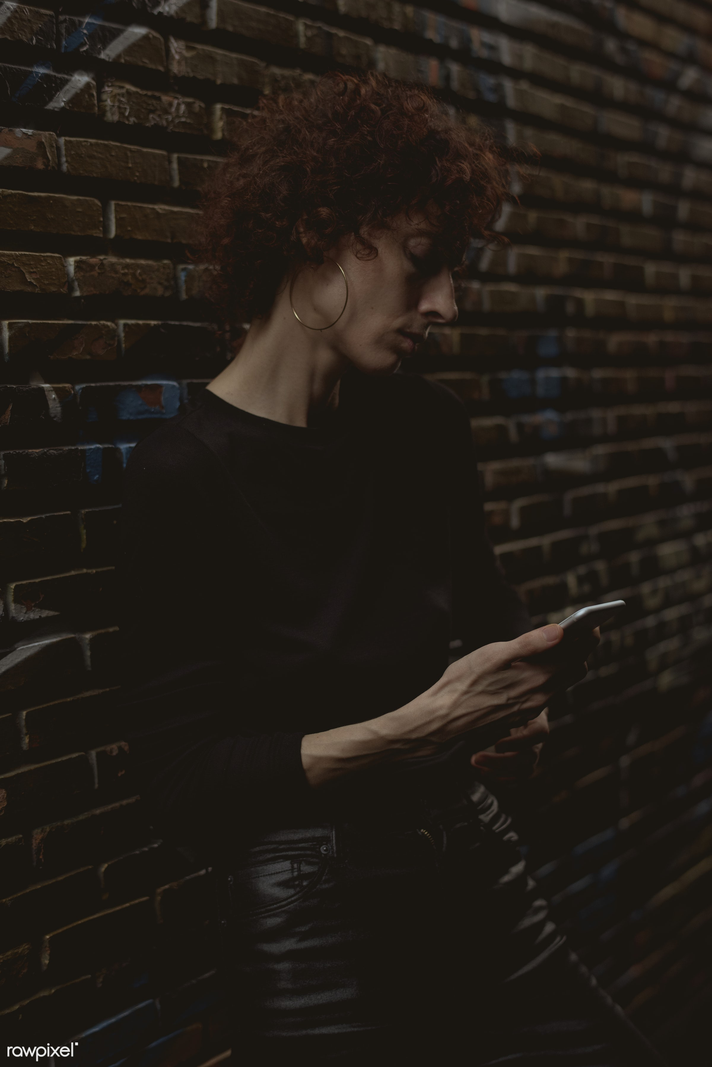 Woman looking at her phone - alley, alone, bar, communication, connection, curly hair, dark, device, digital, digital device...