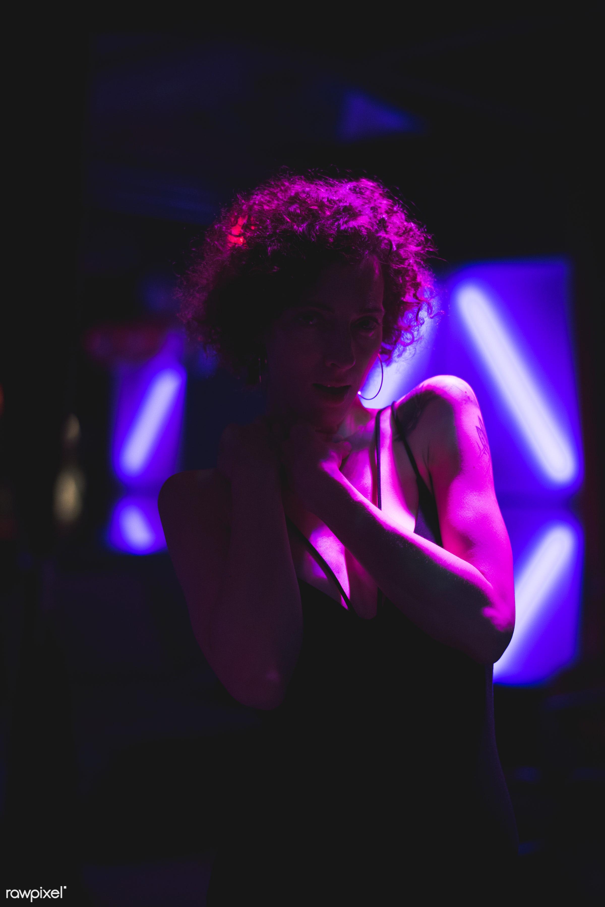Portrait of a woman in a dark bar - alone, bar, caucasian, club, clubbing, curly hair, dark, lifestyle, night, night life,...