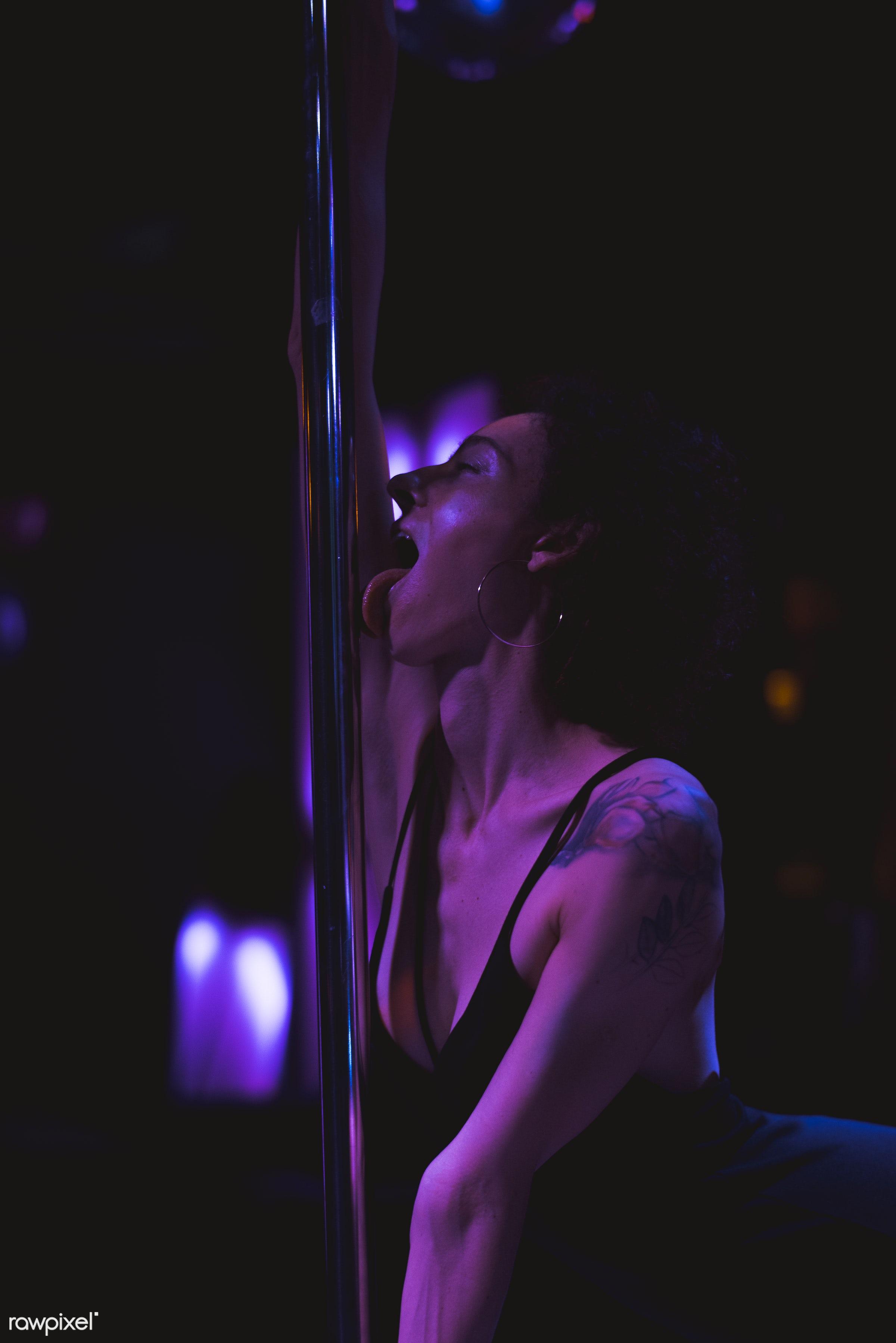 Woman having fun with a stripper pole - alone, bar, cheerful, curly hair, dark, enjoy, fun, lifestyle, night, night life,...