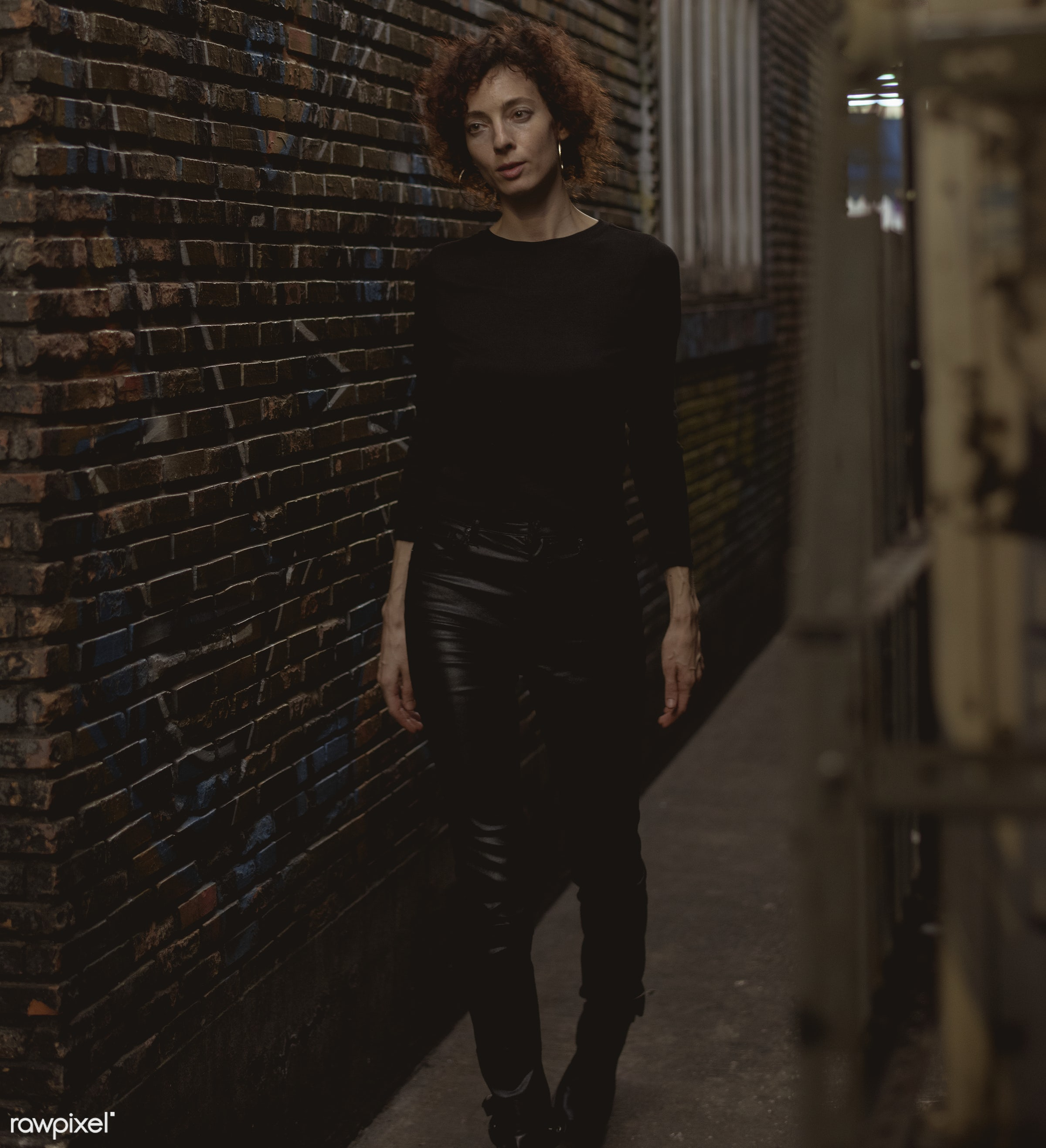 Woman walking through an alley - alley, alone, bar, curly hair, dark, emotion, expression, face, feeling, lifestyle, night,...