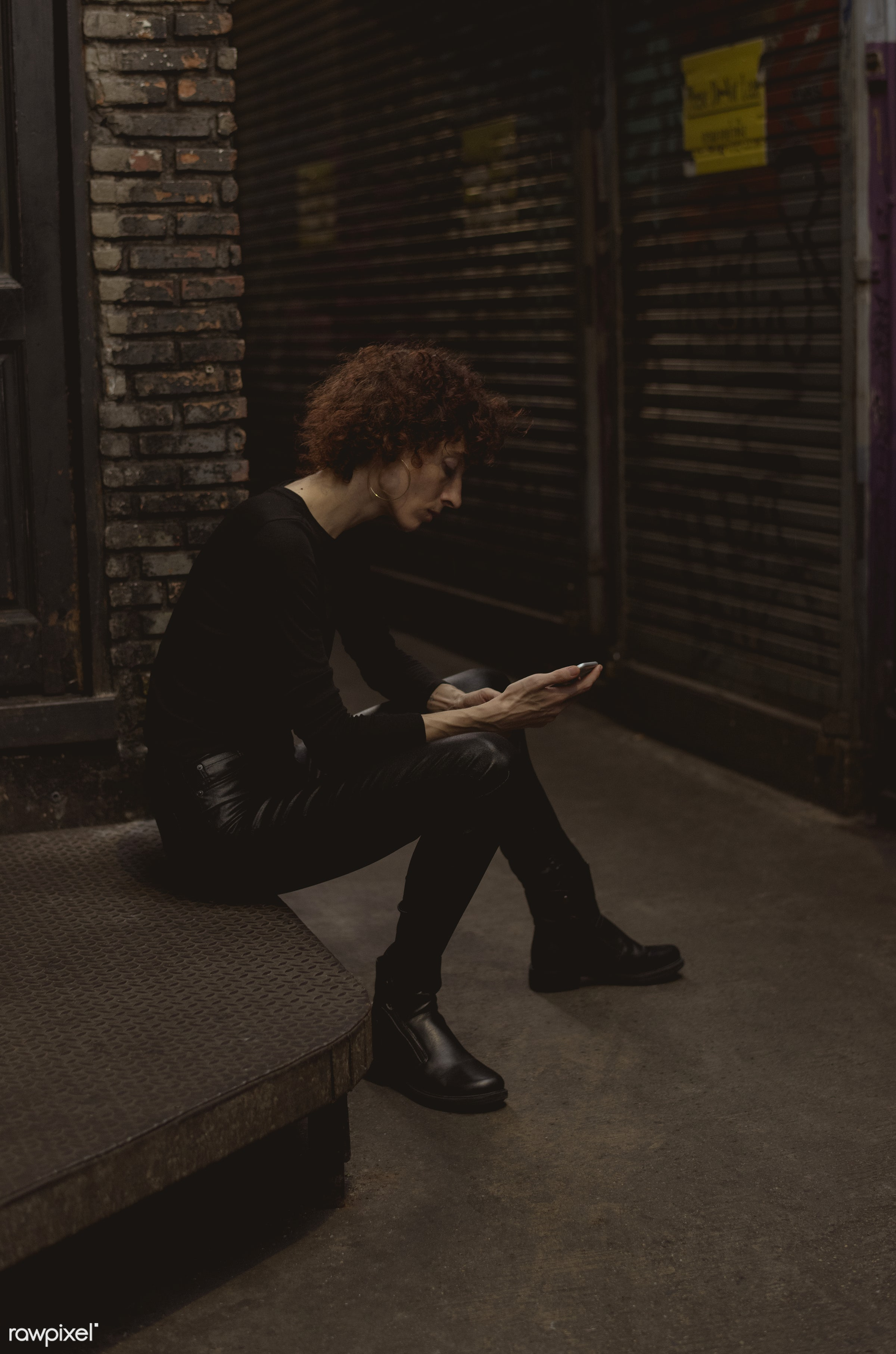 Woman waiting with mobile phone in hand - alley, alone, bar, caucasian, communication, connection, curly hair, dark, device...