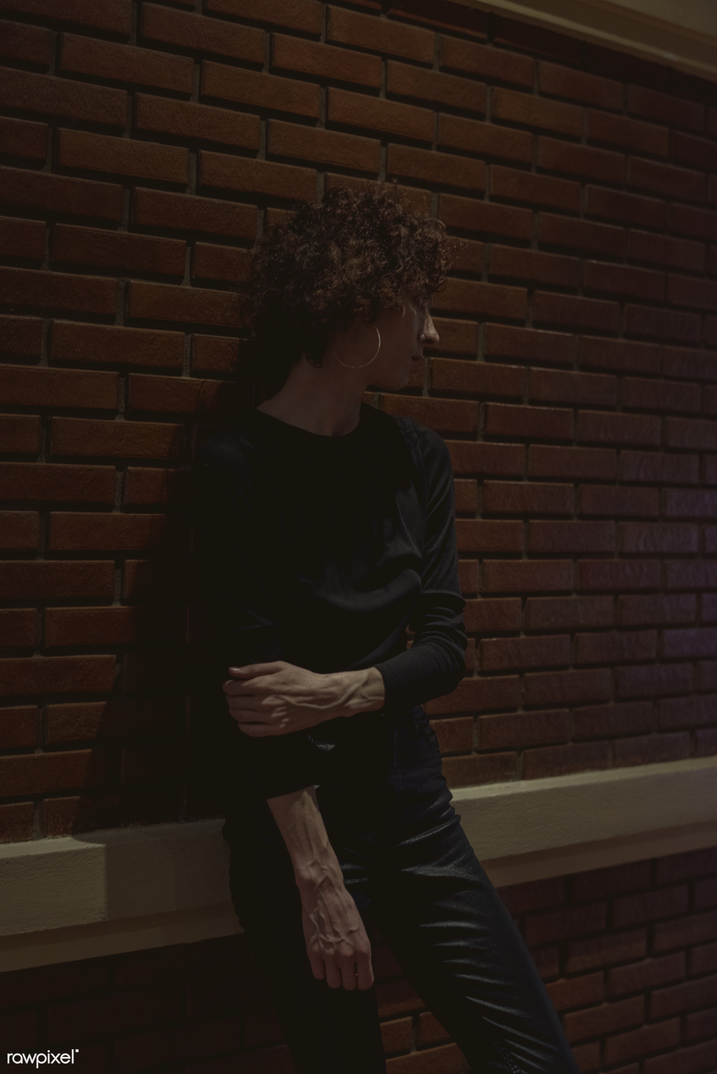 Woman standing by a brick wall - alley, alone, bar, curly hair, dark, emotion, expression, face, feeling, lifestyle, night,...