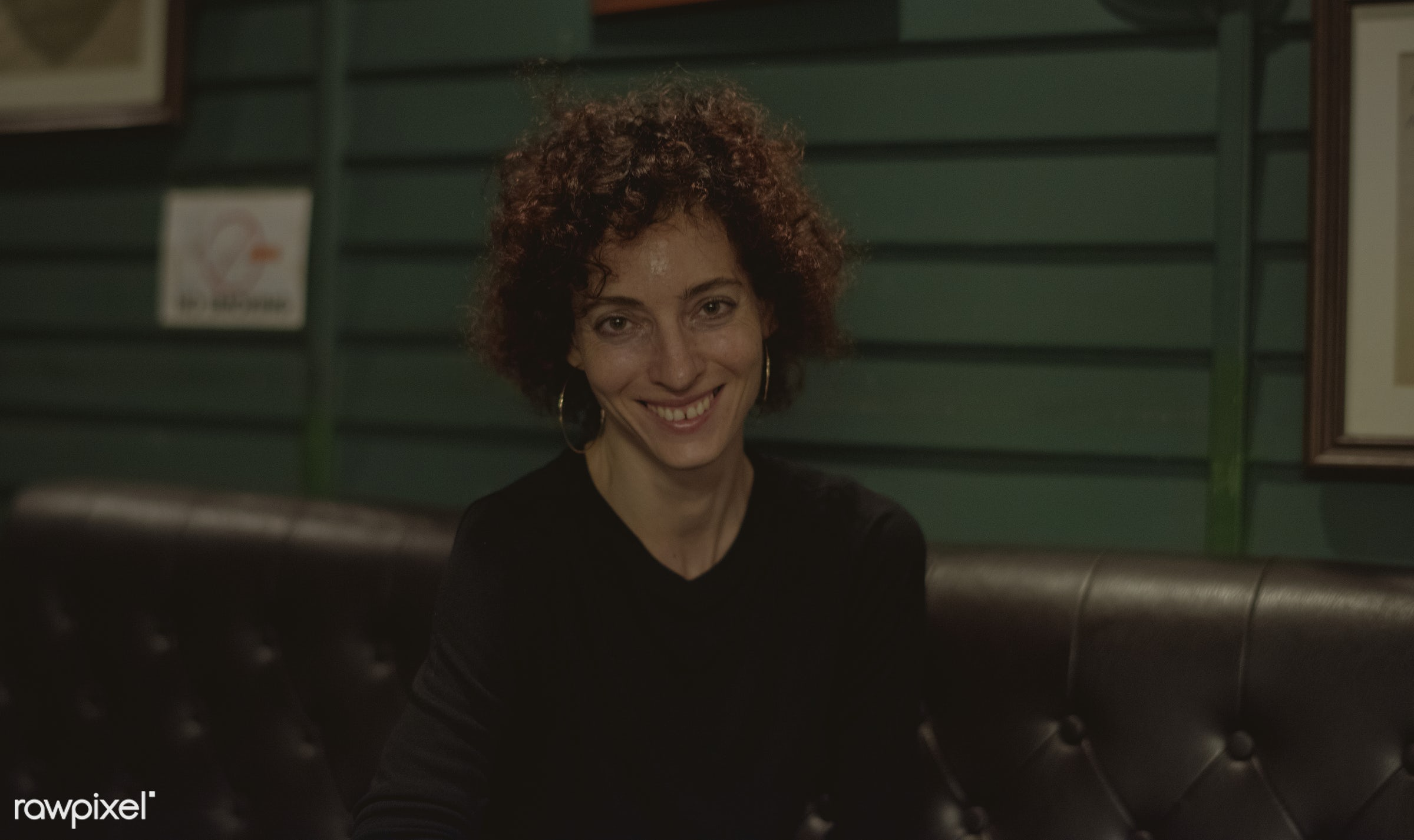 Portrait of Caucasian woman in a pub - alone, bar, caucasian, cheerful, curly hair, dark, happiness, lifestyle, night, night...
