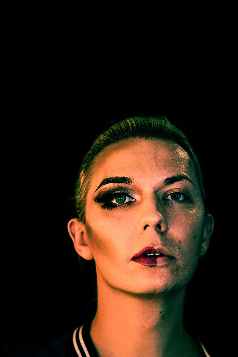 Portrait of a transgender woman with half a makeup on the face