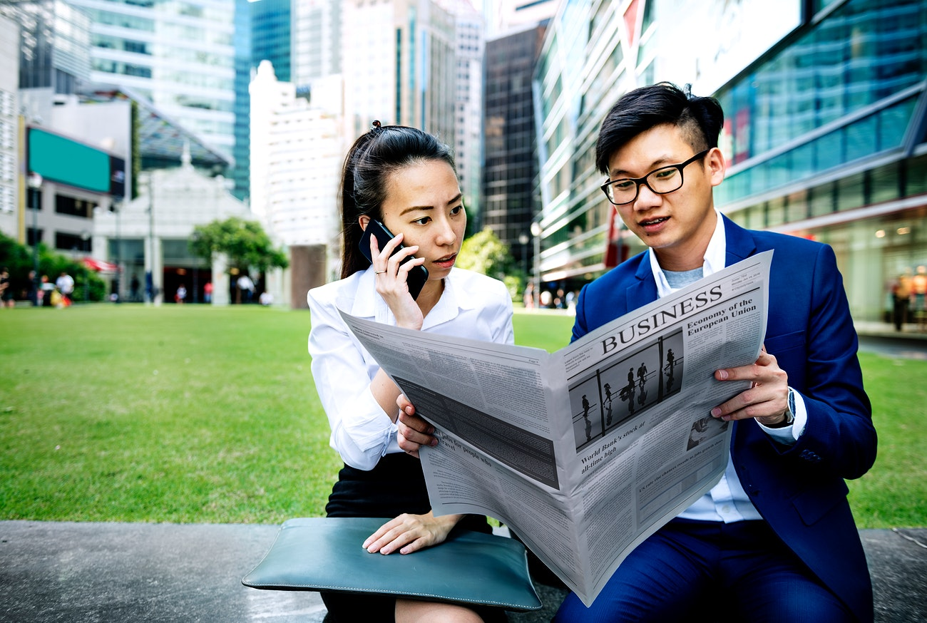 Asian business people reading the newspaper