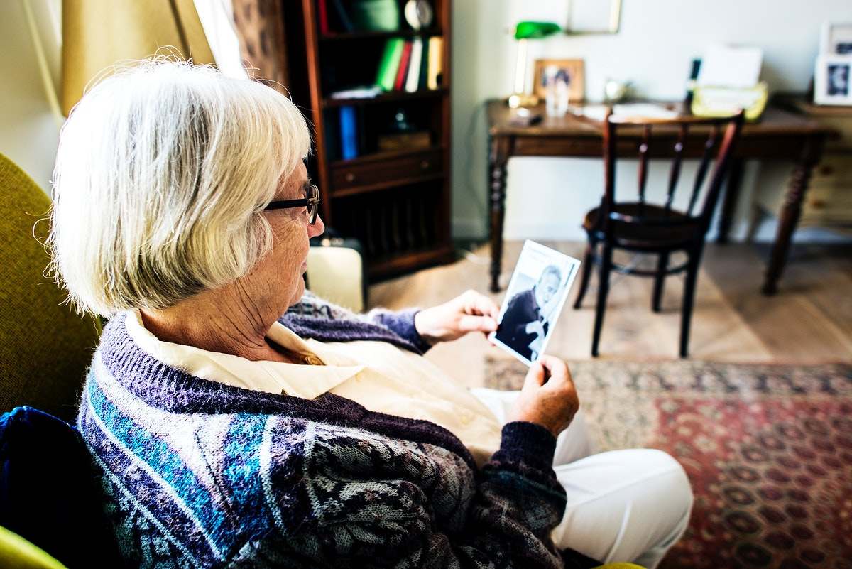 Grandmother sitting and looking at her husband's photo