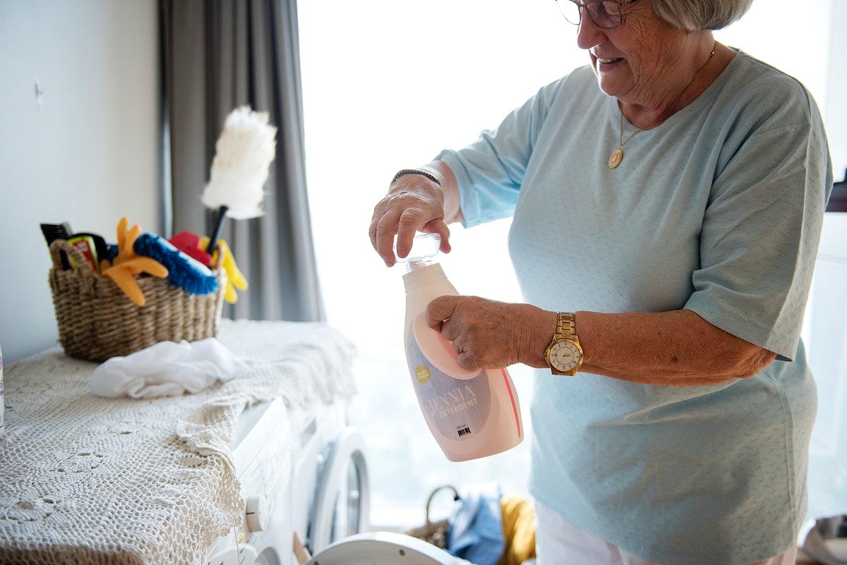 Elderly woman doing a laundry