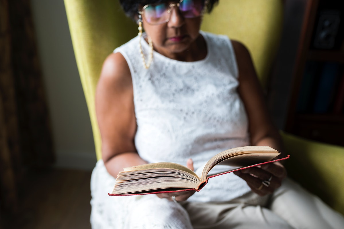 Senior woman reading book in the room