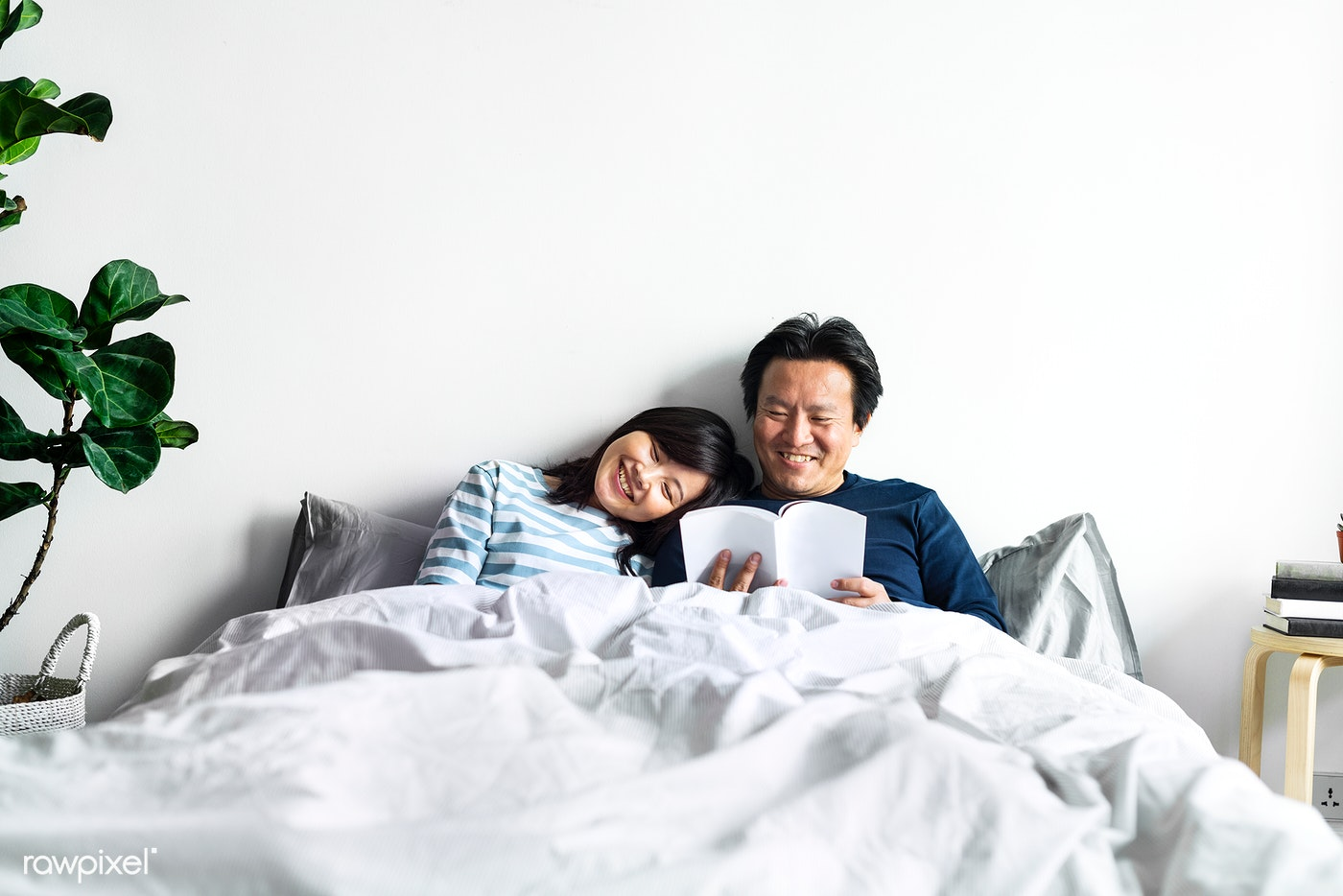 Asian couple relaxing on bed together