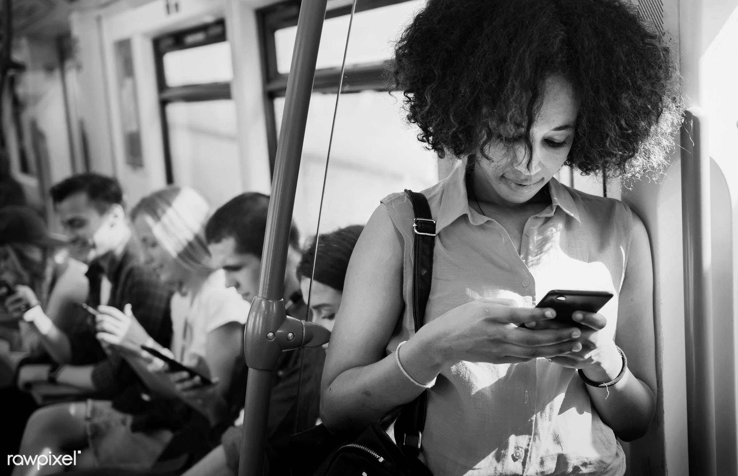 Young woman using a smartphone in a subway - digital, woman, commute, african american, happy, communication, texting, train...