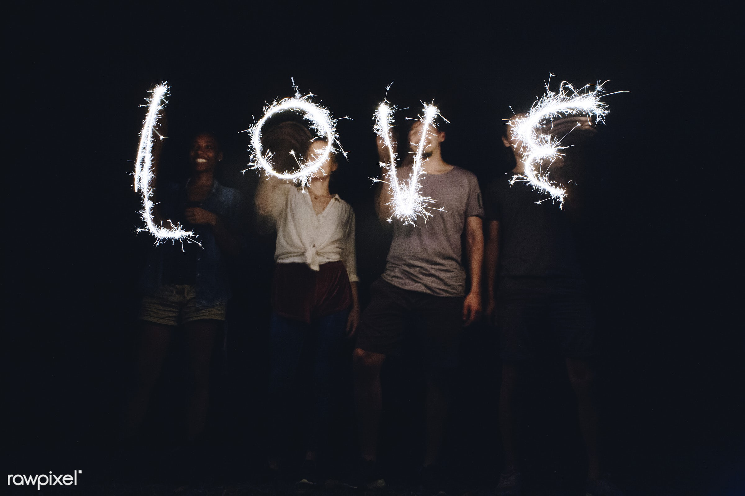 Sparklers forming the word love - adult, american, bright, burning, carefree, casual, celebration, day, enjoy, event, female...